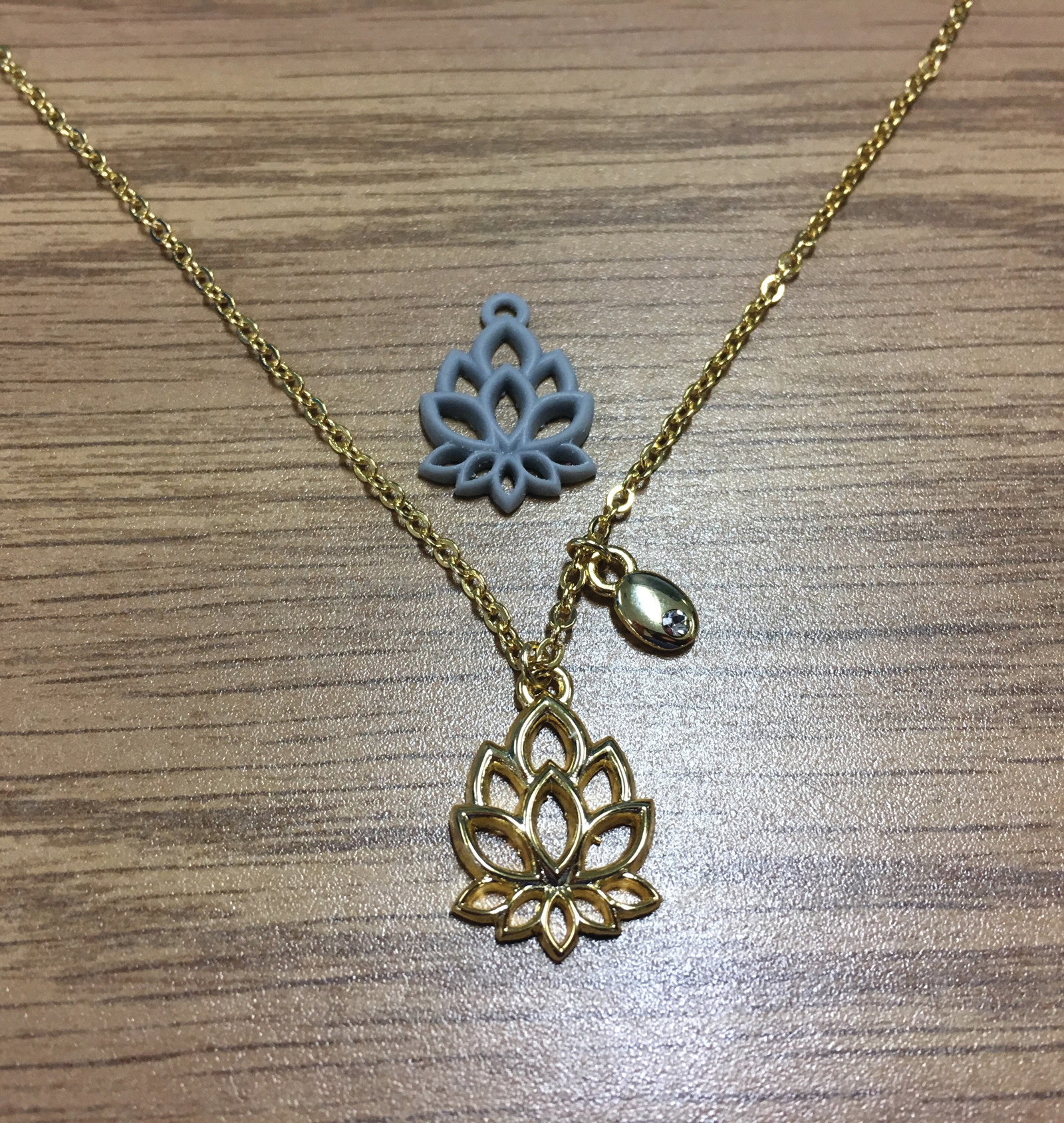 "BEFORE AND AFTER: The 3D printed ""tranquility"" pendant before and after it is plated."