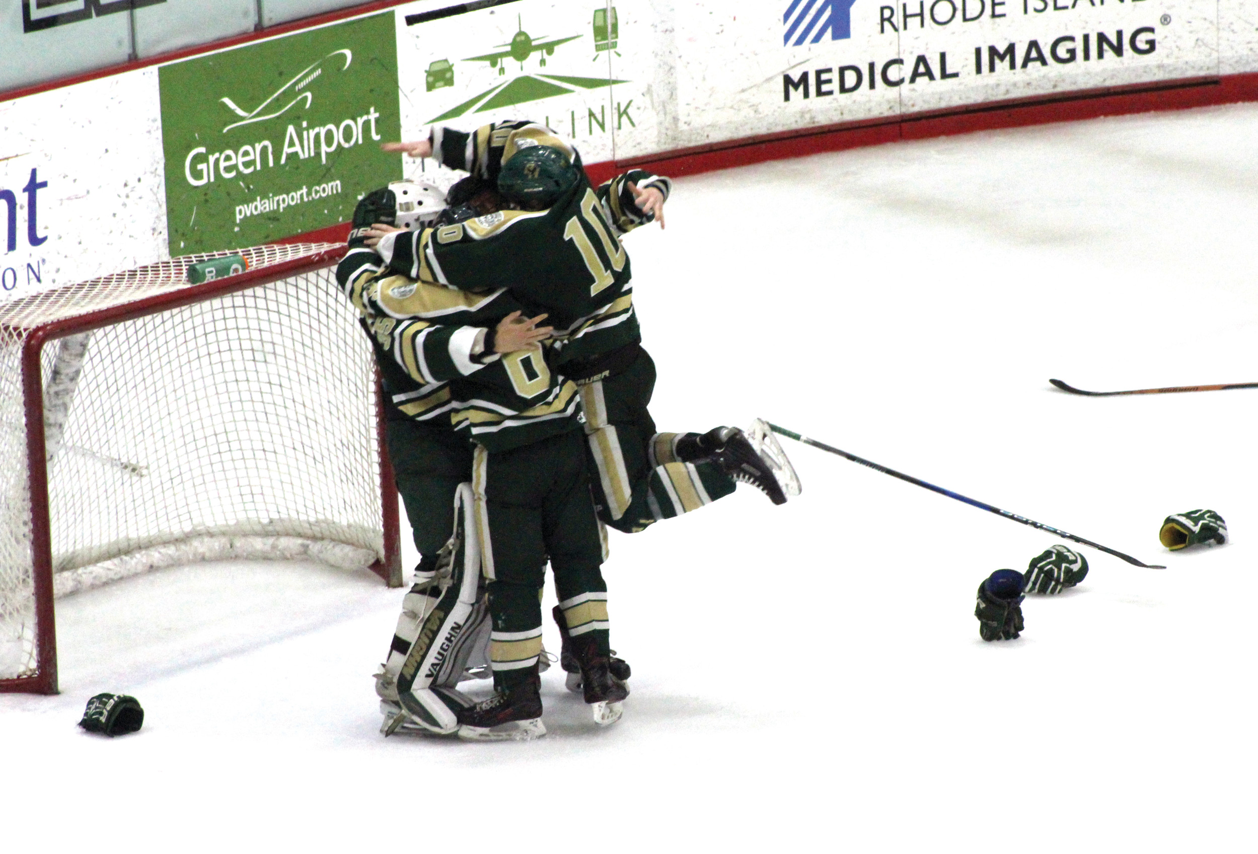 Hendricken seniors Pat Creamer (10) and Michael Shaw (6) celebrate with goaltender Patrick Gribbin after the final buzzer on Saturday.