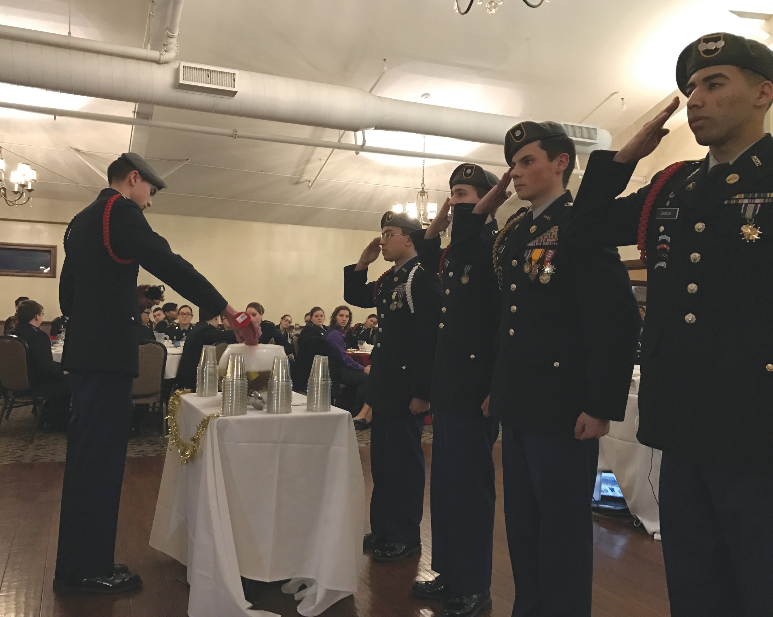 CHEERS TO THE GROG: Members of the JROTC Honor Guard watch as another ingredient is added to the punch bowl at the JROTC military ball on March 11.