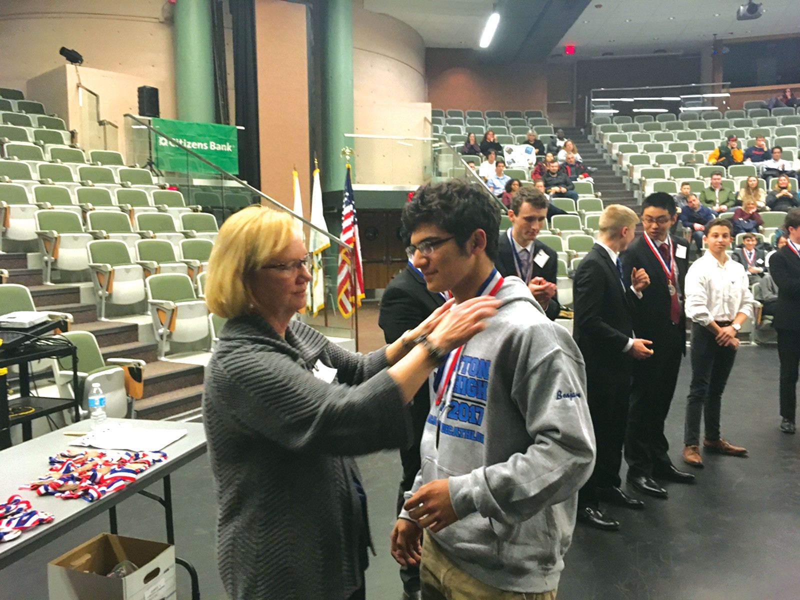 THREE MEDALS: Junior Benjamin Budway is presented with one of his medals from Decathlon board member Paula Pratt. Budway earned three medals at the competition.