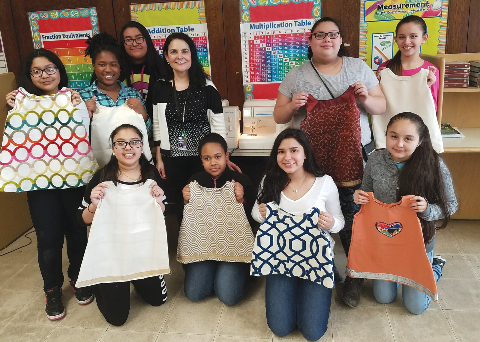 LEARNING SKILLS THAT WILL HELP OTHERS: Pictured with their machines and some current clothing projects are some of the Sew Bain club members, along with their advisor, Rachel Bousquet and club volunteer, Naraly Barrious. The members of the club are Vashani Auguste, Diana Custodio, Abrina Estrada, Abby Morales, Brianna Munrayos, Jamie O'Brien, Leslie Pineda, Luz Marie Plasencia, Stacey Rios, Claudianna Rocher and Adia Sarr.