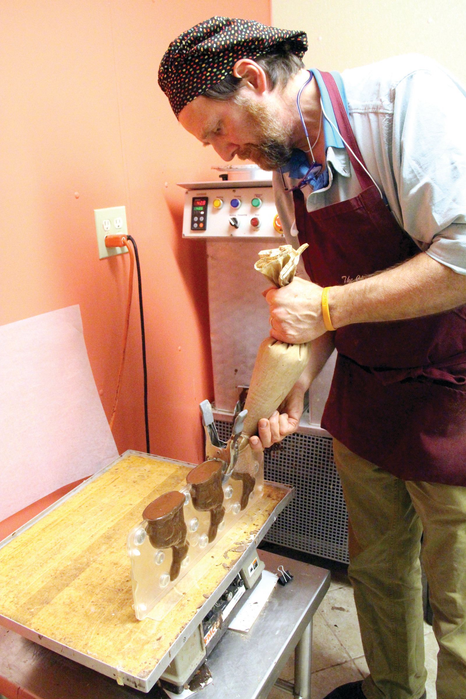 BUNNY INCUBATOR: Dave Schaller squeezes melted chocolate into bunny molds at The Chocolate Delicacy. He and his wife, Marie, have already made more than 2,400 bunnies to meet the Easter demand.