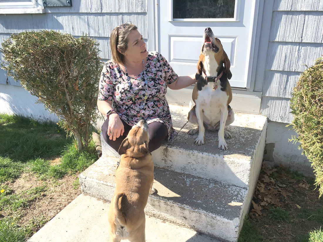 CURRENT HOME: Amy Tellier sits on the porch of her Warwick home with two of her six dogs. She's currently fighting to keep all six.