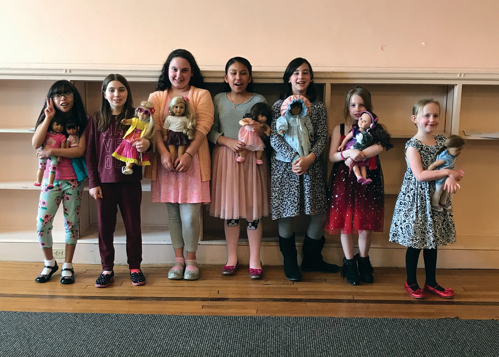 HELLO, AMERICAN GIRL DOLLY: Left to right, Celine, Anya, Jordan, Liliana, Isabella, Samantha and Nora, pose happily with with their special friends at the American Girl Doll tea party on April 15 at William Hall library.