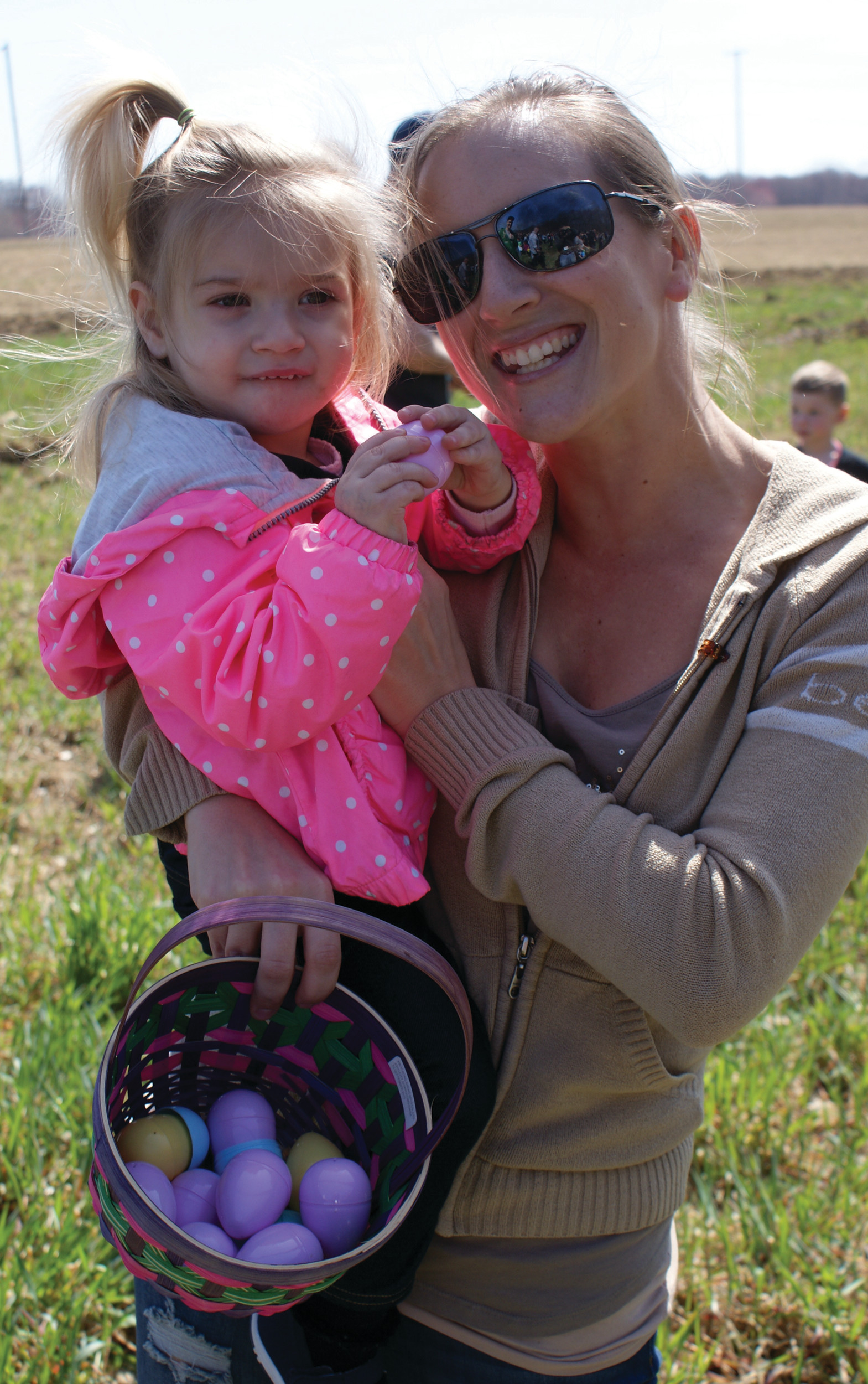 MOMMY AND ME: Young Kinslee Anderson, age 2, of Cranston shows off her eggs she collected at the Easter Egg Hunt while being held by her mother, Jessica.