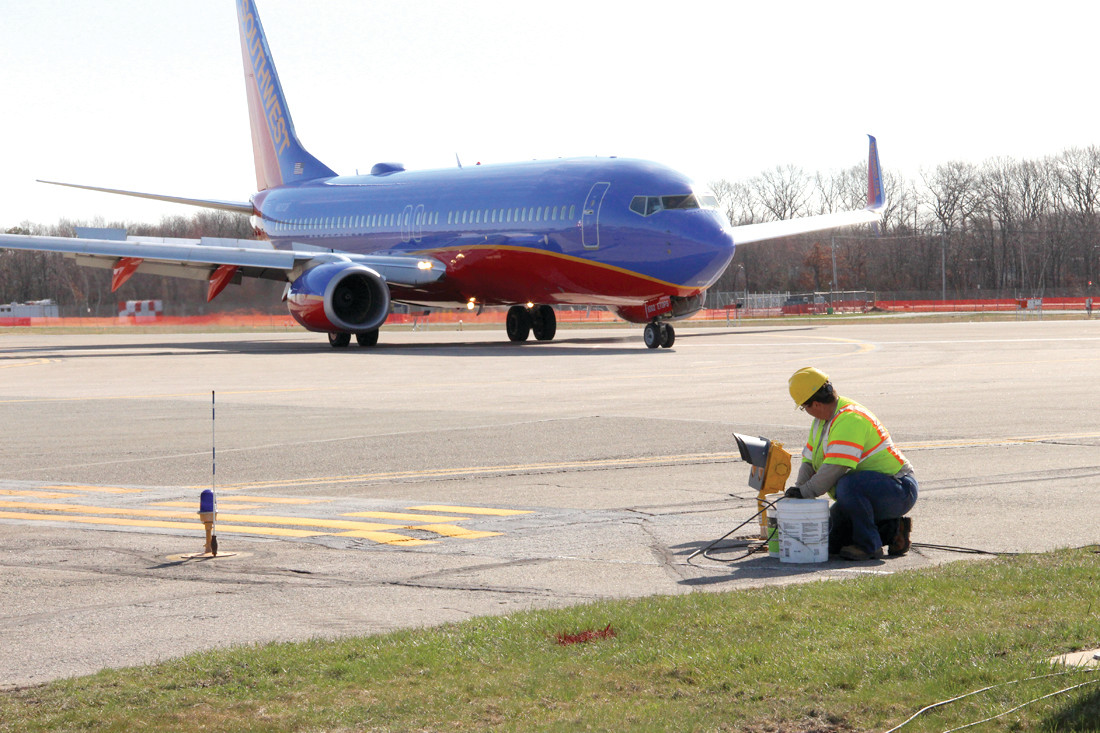 TAXIWAY LIGHTS: Julie Bailey of Cardi Construction isn't interrupted by a Southwest jet as she works on taxiway lights.