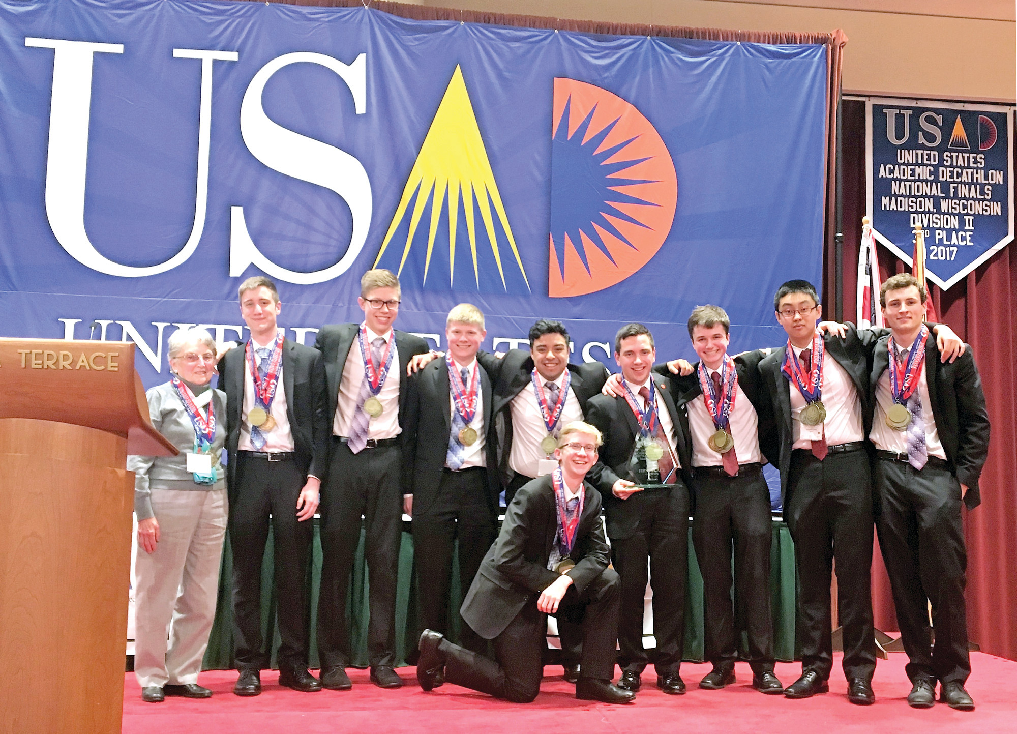 DIVISION WINNERS: The Hendricken Academic Decathlon team placed first in the Division 11 in the United States Academic Decathlon held last week in Madison, Wisconsin. Pictured from left are coach Sister Carol Ann Murray and team members Connor Milson, Darragh Harkin, Alden Pratt, Jaidan Idarraga, Cory Morris, Dylan Temel, Steven Huang, Ryan Brady and (kneeling in front) Mitchell Boyer.