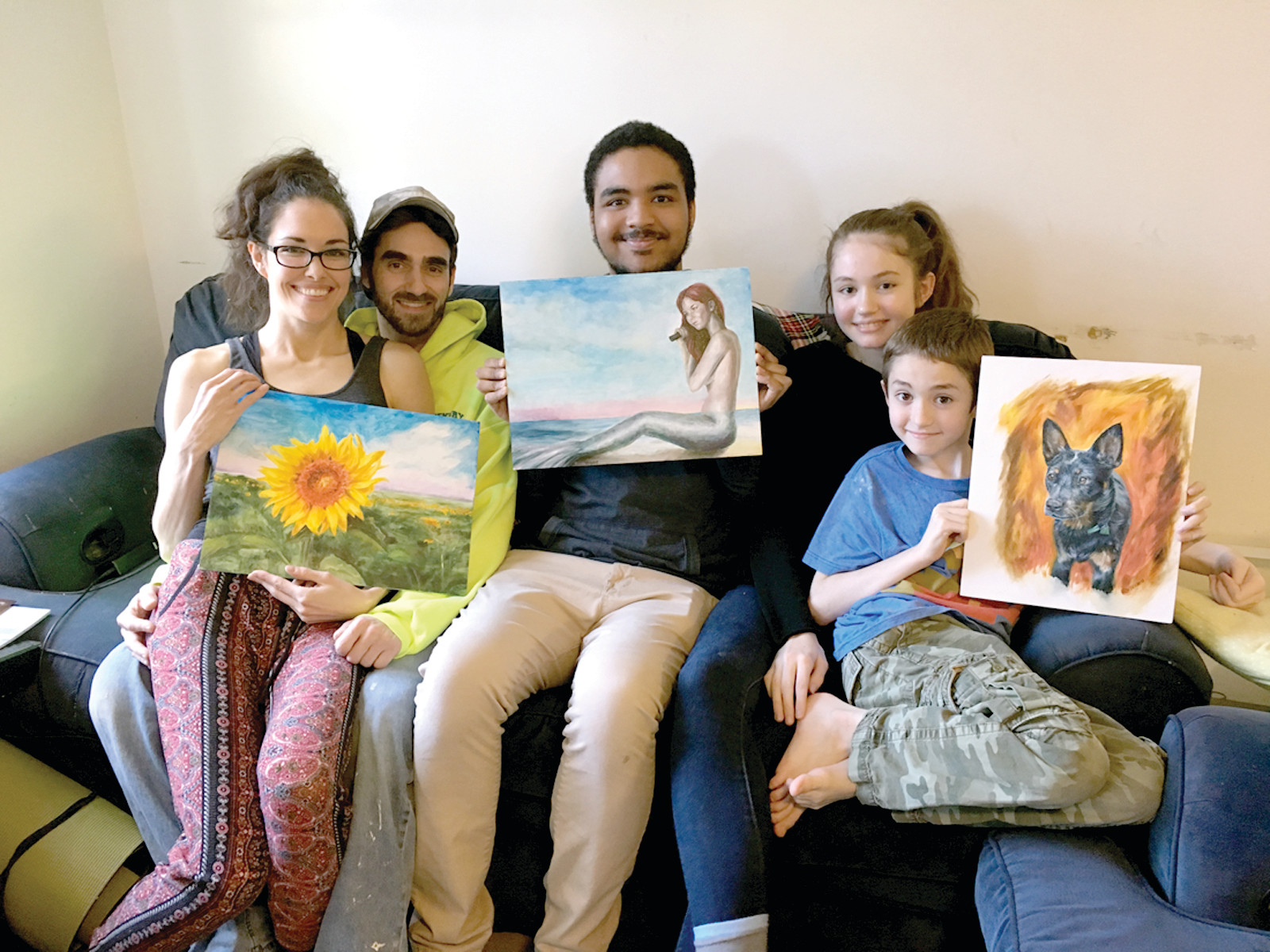 ART IN THE FAMILY: Artist Rhiannon Smith (far left) gets some help from fiancé Jason Musone and her children, Clayton, 20, Selene, 14, and Wesley, 10, in showing off a few pieces of her artwork.