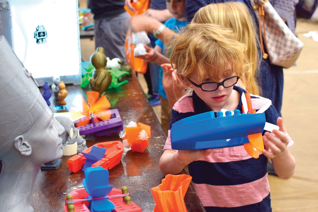 NEVER TOO YOUNG TO APPRECIATE A WELL-DESIGNED BOAT: A spectator at the Robot Block Party explores 3D Printed paddleboats created by members of the Ocean State Maker Mill.