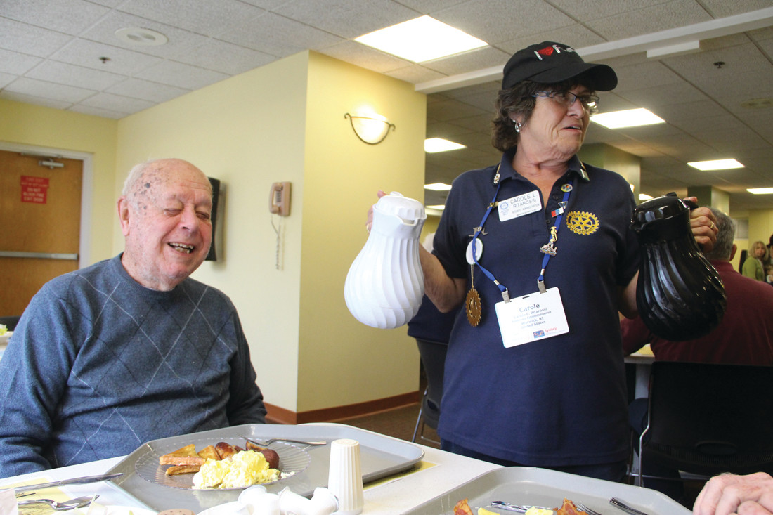 DOUBLE JUGS: Carole Ritarossi was among the more than two dozen Rotarians who poured coffee and bused tables for the club's May Breakfast hosted by Kent Hospital. Waiting for his coffee is Leonard Maynard, who has been a member of the club since 1966.