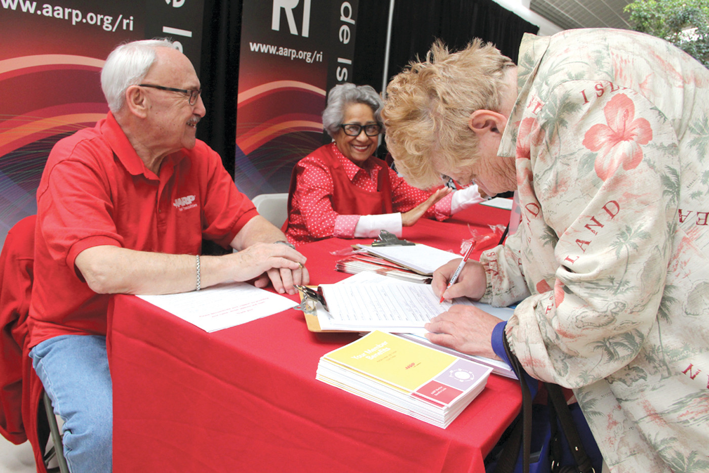 Marianne Whalen of Blue Cross Rhode Island assists Sanford and Joyce Miller. Blue Cross was a major sponsor of the expo hosted by Prime Time magazine.