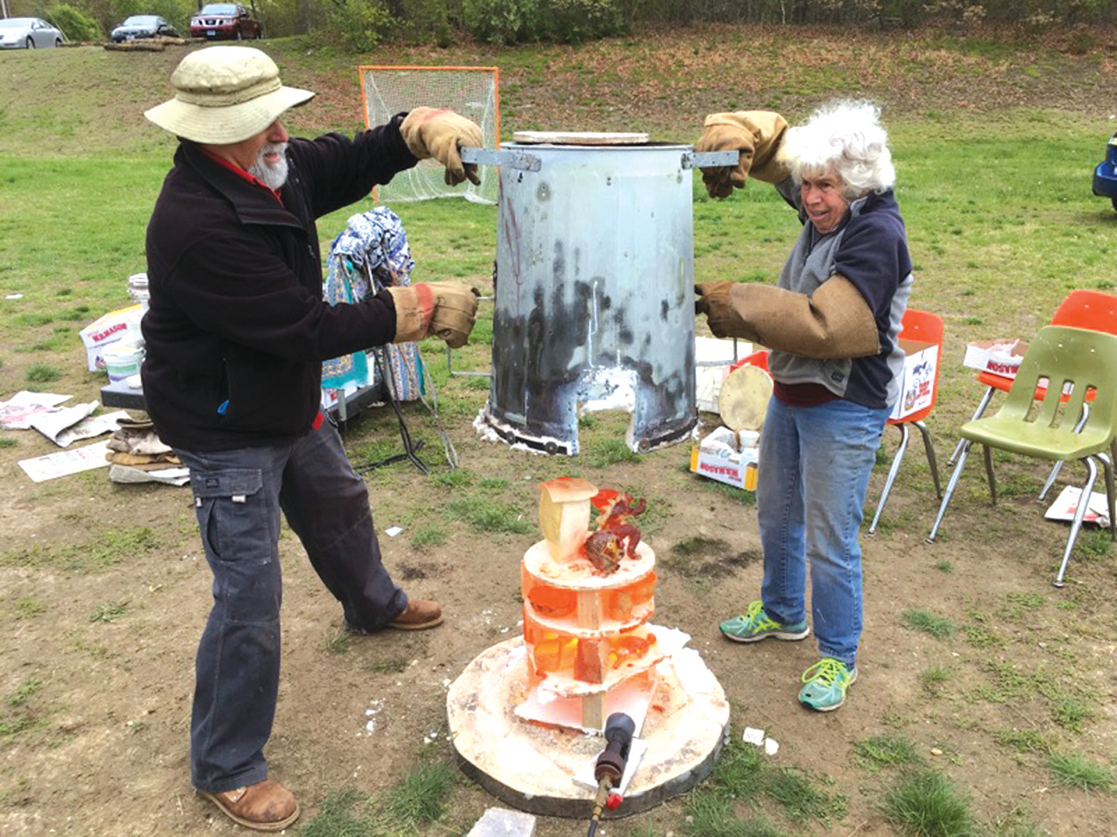 PIPING HOT: Artist Kate Champa needed assistance to lift the outer kiln cover to expose the still red hot student pieces of raku art.