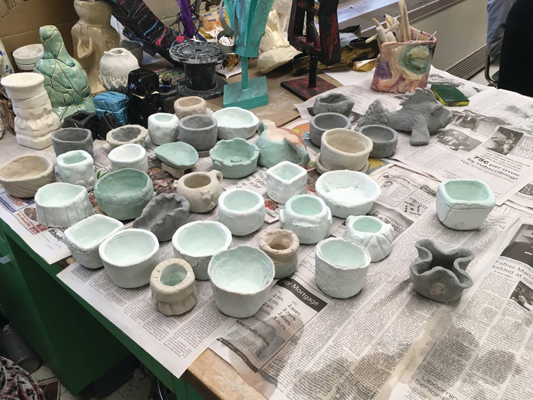BEFORE: A collection of students' raku pottery that has been dipped in glaze and awaits firing.