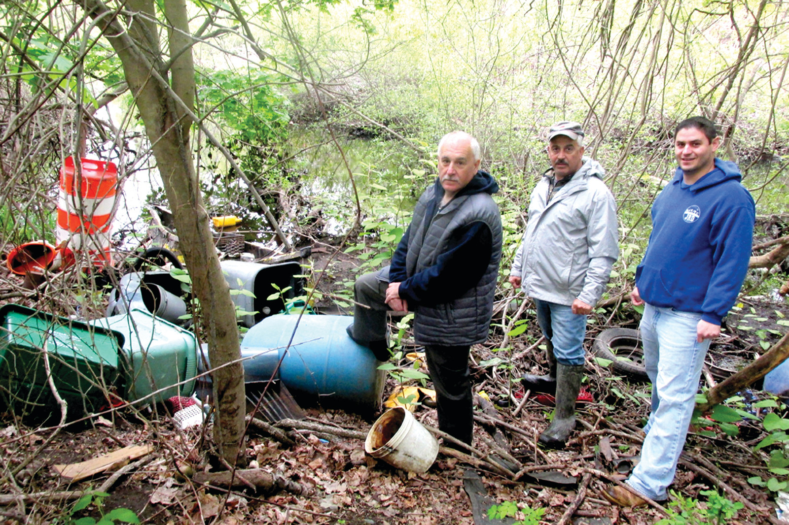 DAMAGING DEBRIS: Johnston Mayor Joseph Polisena, who is joined by Michael Maddalena of the Pawtuxet River Authority and District I Councilman Richard J. DelFino III, puts his foot on this large garbage container and looks around at other debris that people continue to dump alongside the once beautiful waterway.