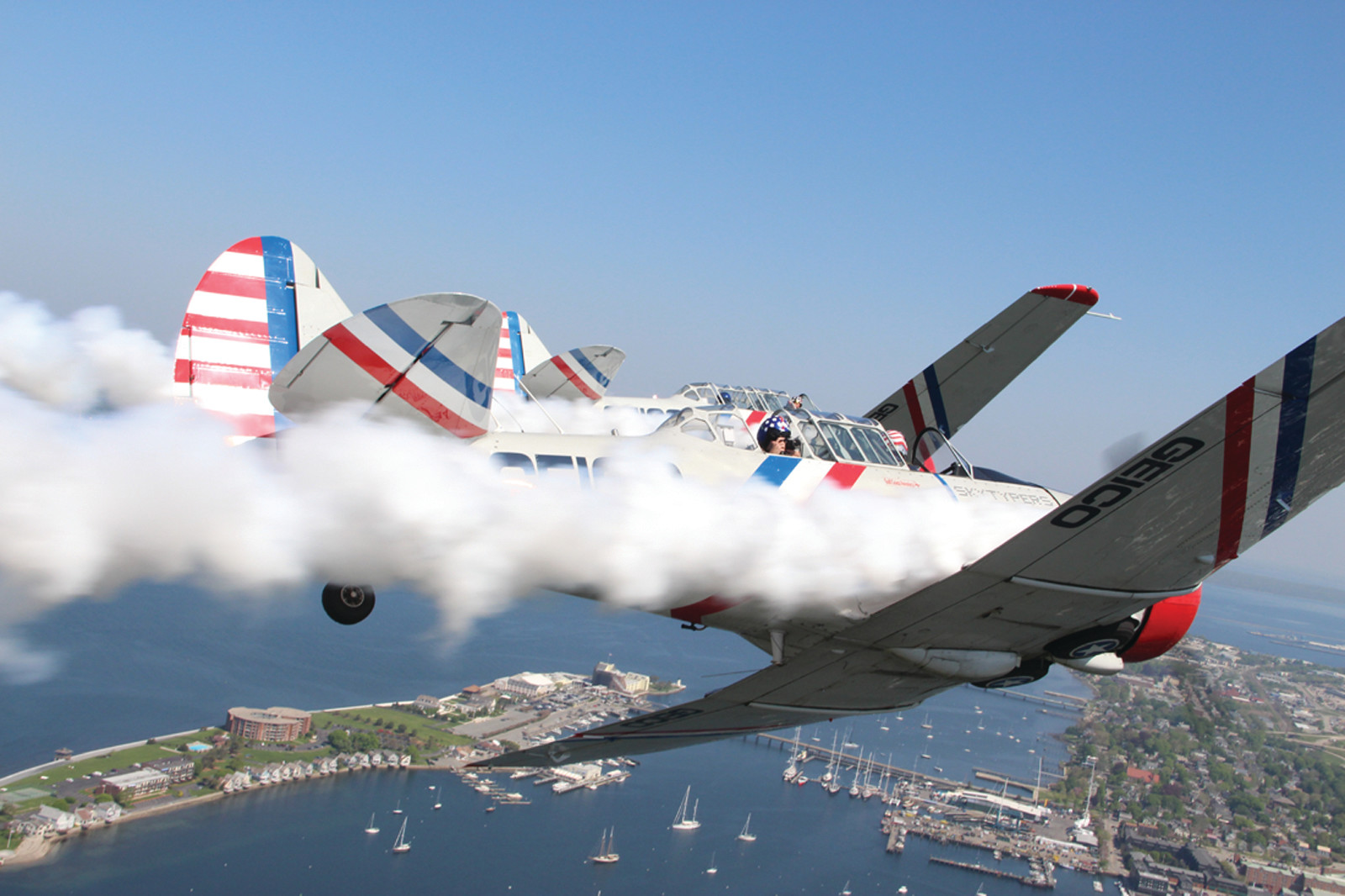 "WRITING OVER NEWPORT: Flying in tight formation, a pair of Geico Skytypers leave a trail of smoke over Newport Harbor. Giving a ""thumbs up"" for the plane to take off is Tom Daly. Pilot Chris Orr is pictured after returning to Quonset."