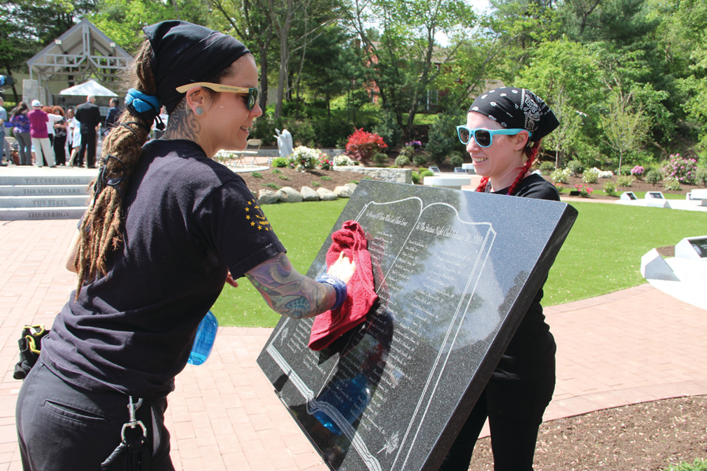 GETTING READY: Shanna Roma and Jennifer Donazio polish a plaque in preparation for Sunday's dedication.