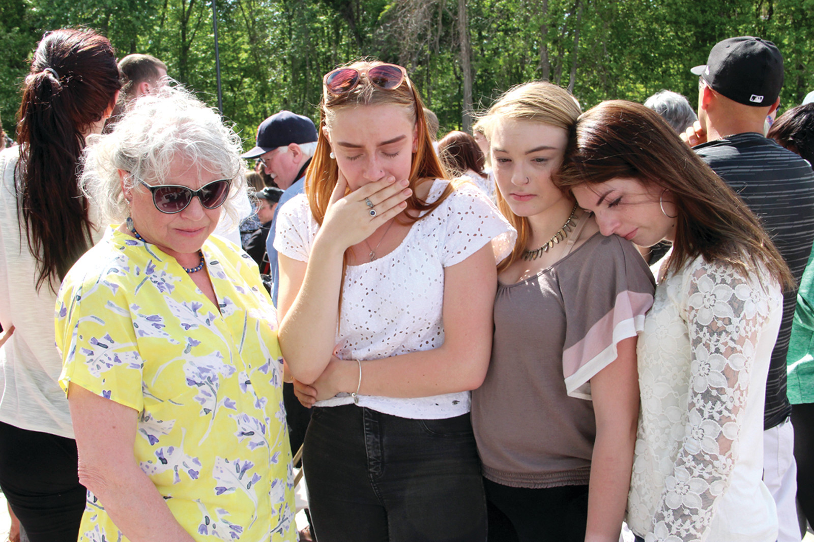 REMEMBERING MIKE: Dana Christman (left) consoles her granddaughters Maria and Emily Fresolo and grandniece Toni. Mike Fresolo died in the fire when Maria was a toddler. Christman said it was three weeks after the fire before Fresolo's death was confirmed.