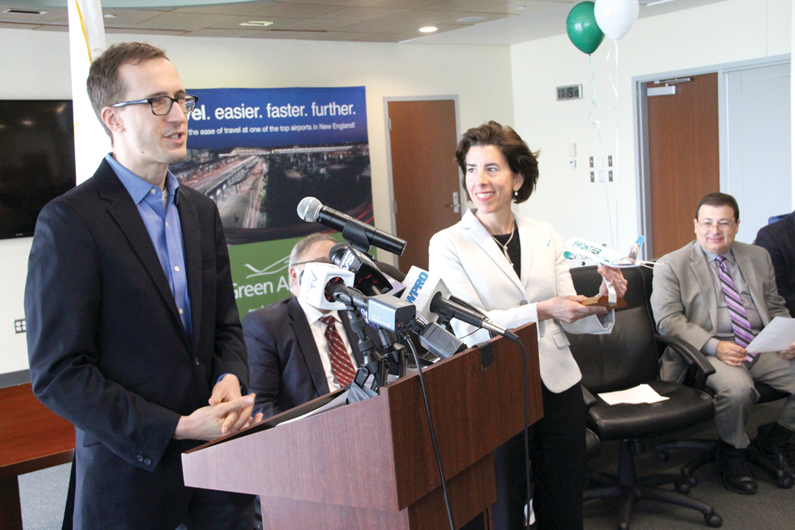 COMING TO GREEN: Daniel Shurz, Senior Vice President – Commercial for Frontier Airlines, outlines the service the company will bring to Green Airport starting Aug. 14 as Gov. Gina Raimondo looks on.