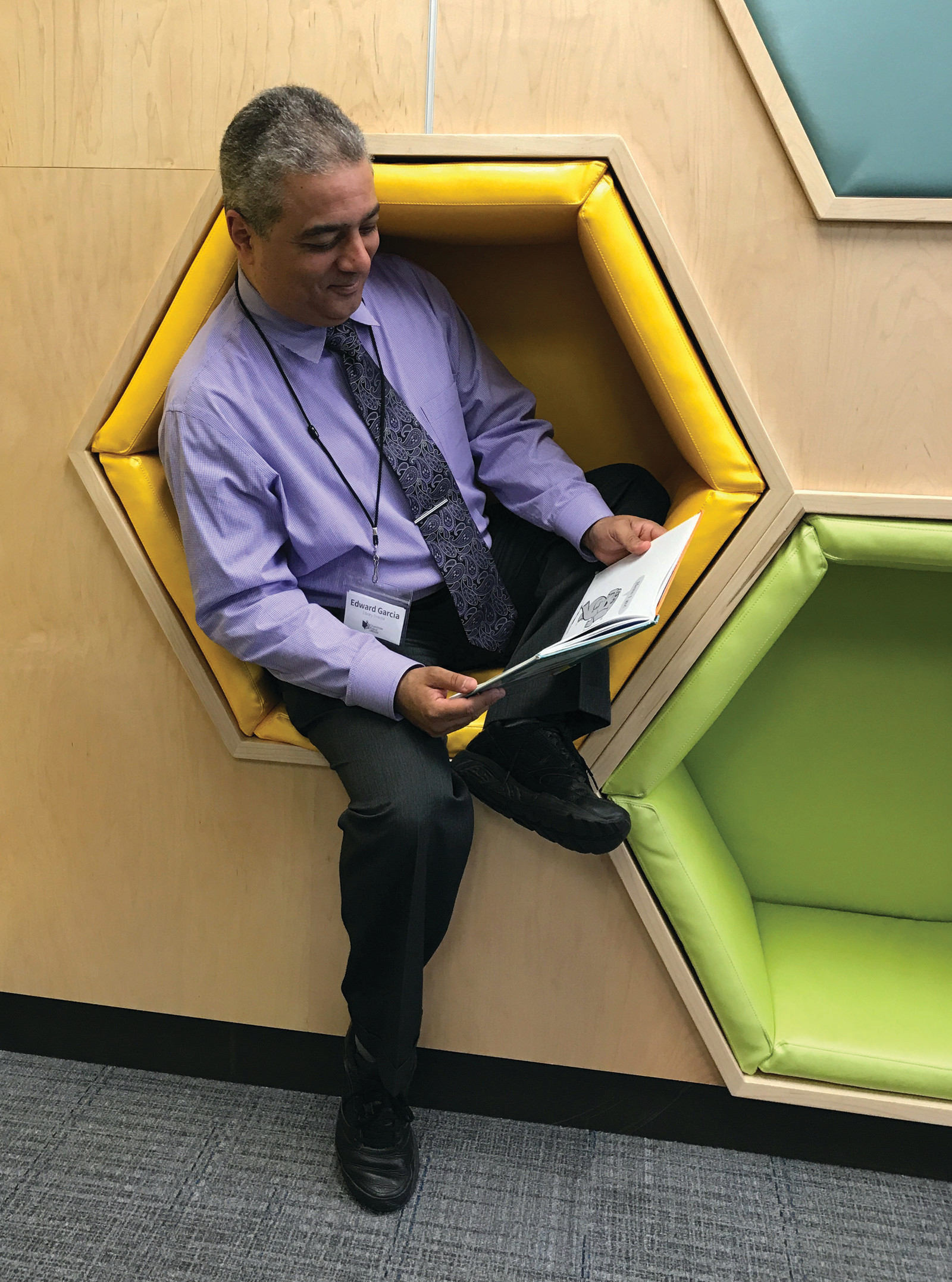 EVERYONE LOVES THE HONEYCOMBS: Director of Cranston Libraries Ed Garcia was caught taking a reading break in the new wall of honeycombs.