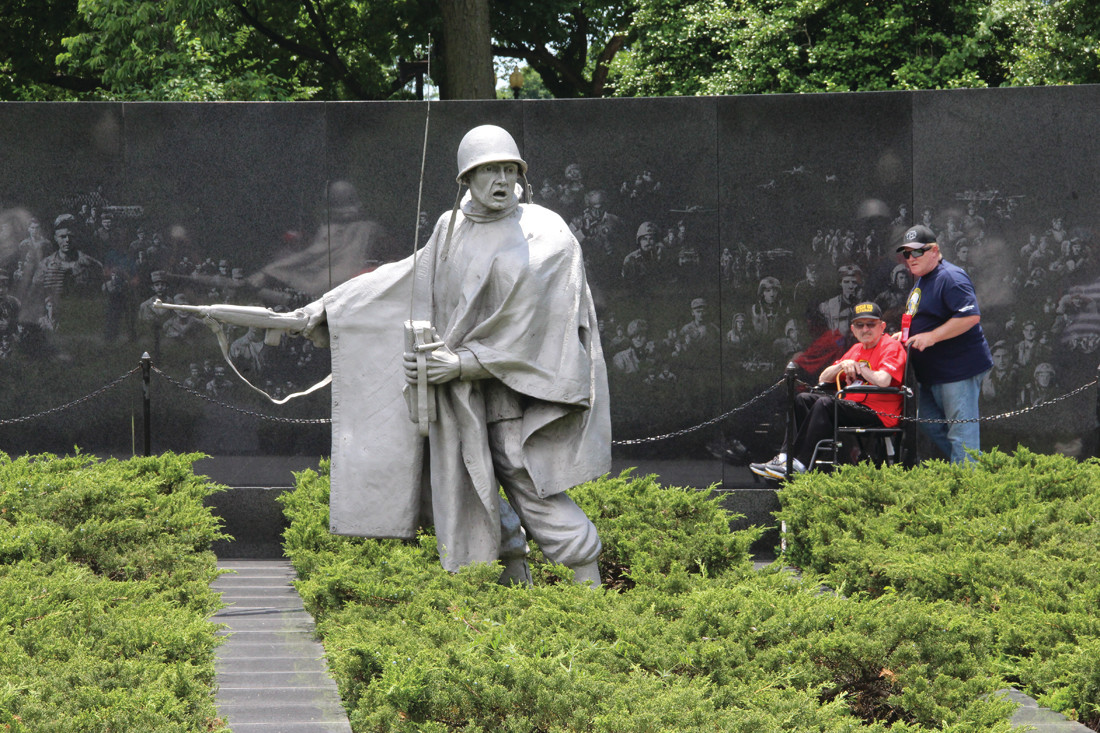 MEMORIES OF BATTLE: A veteran and guardian from the Honor Flight tour the Korean War Memorial.