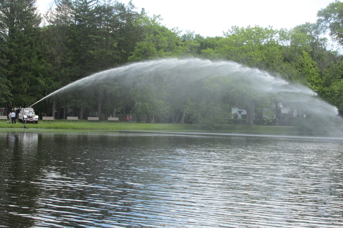 "SPRAY AWAY: This spray of water over the pond inside Johnston War Memorial Park came from a 1939 Ahrens-Fox Fire Engine that classic collector Richard ""Dick"" Shappy brought to the Ocean State Vintage Haulers Show Sunday."