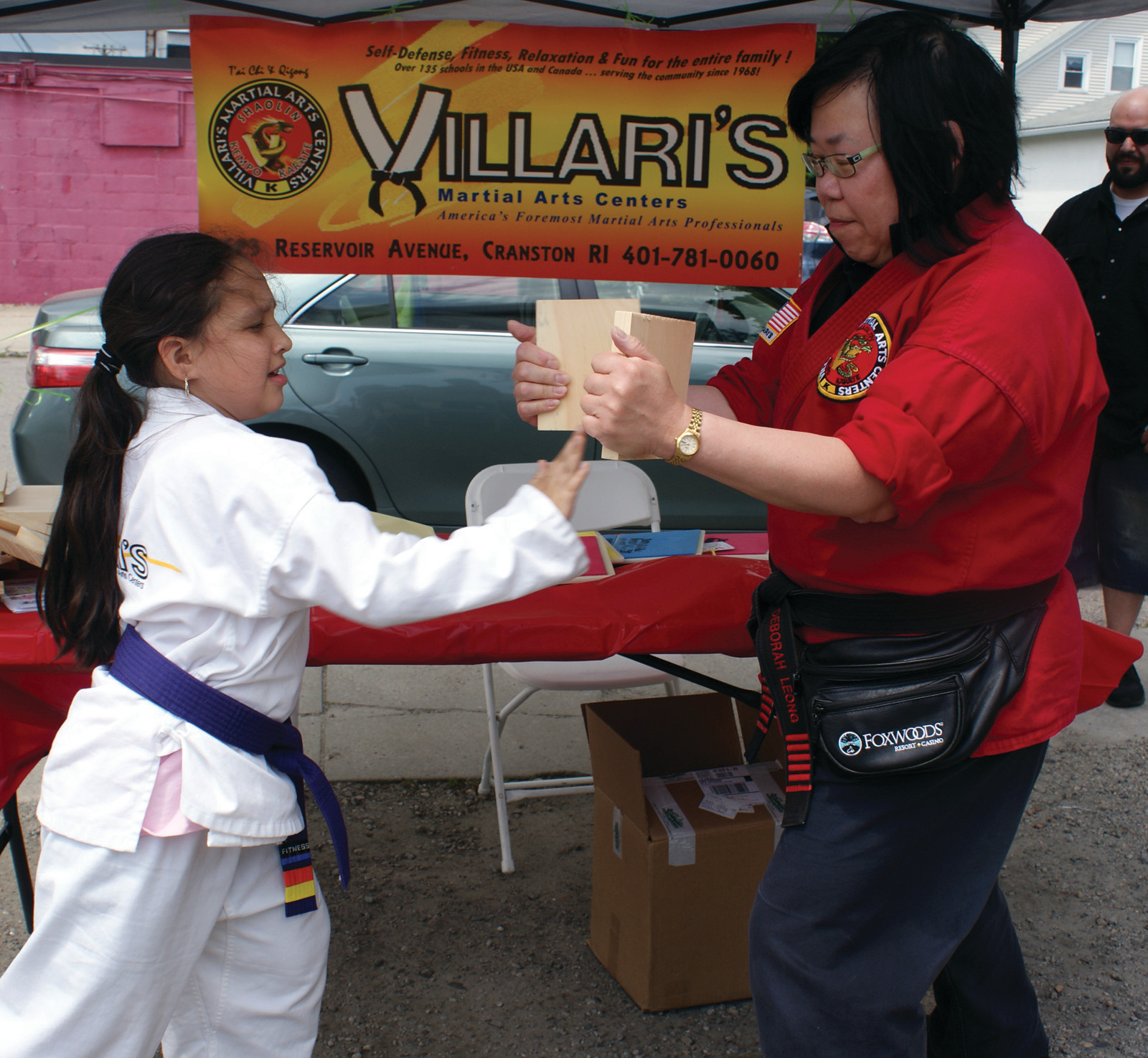 BREAKING BOARDS: One of the many attractions at Family Fun Day at the New England Slush Company was the booth provided by Villari's Martial Arts Centers, located on Reservoir Ave. Pictured is Purple Belt, Eilanna Arce, age 7, breaking a board in half which was held by Master Deborah Leong, a 6th Degree Black Belt.