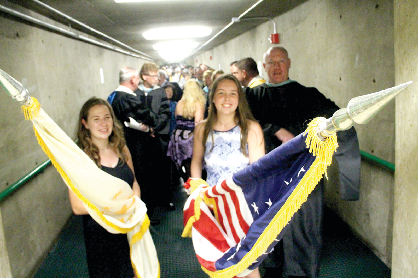 TAKING THE LEAD: With Principal Gerald Habershaw, the mayor and other officials behind them, flag bearers prepare to lead the procession into the CCRI field house.