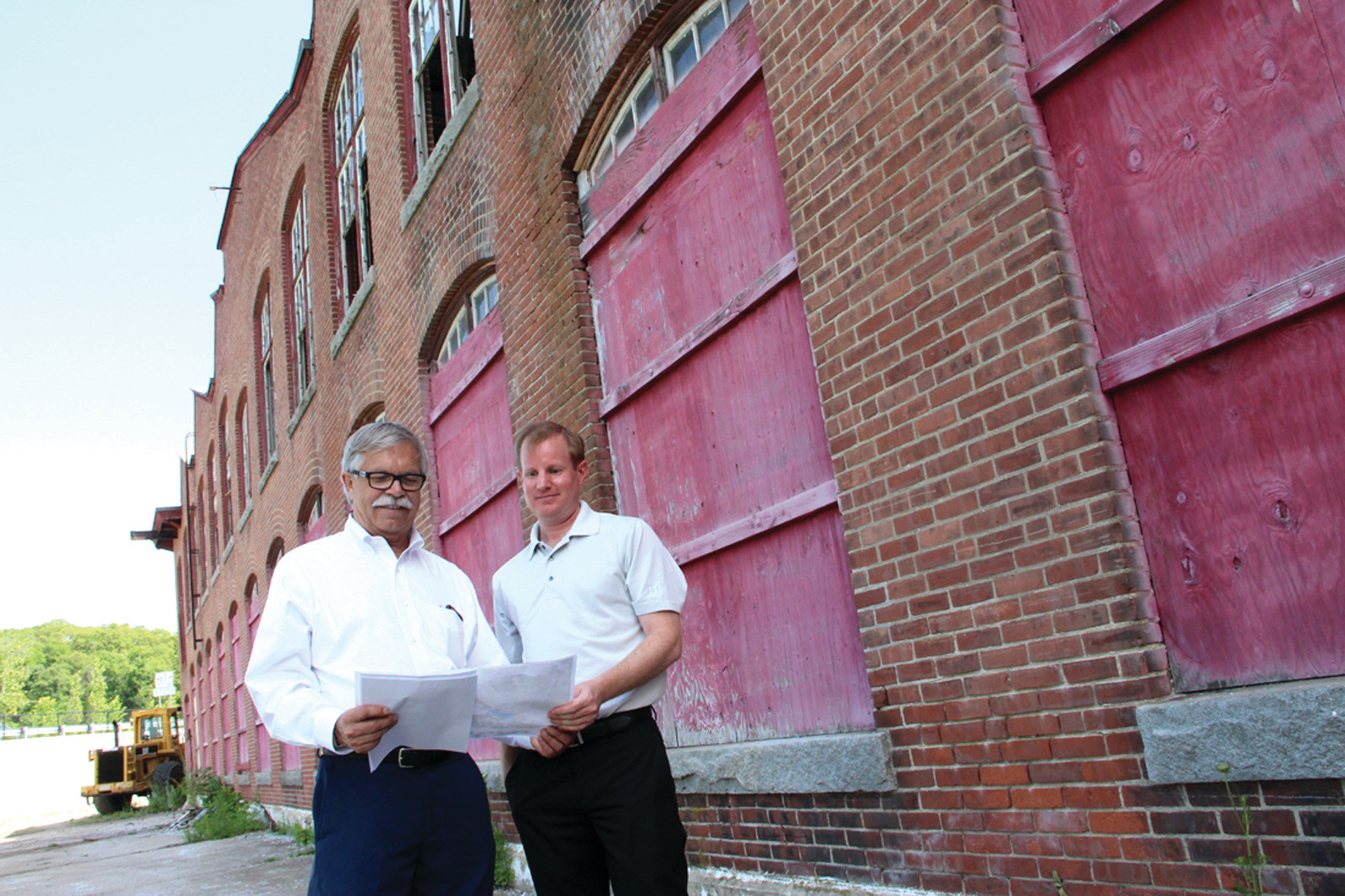 LOTS OF SPACE: Mark Shaw, president and CEO of AAA Northeast, and Peter Buhl Jr., AAA manager of real estate planning, outside the saw tooth building that was once part of the Apponaug Mill. AAA bought the building at auction yesterday.