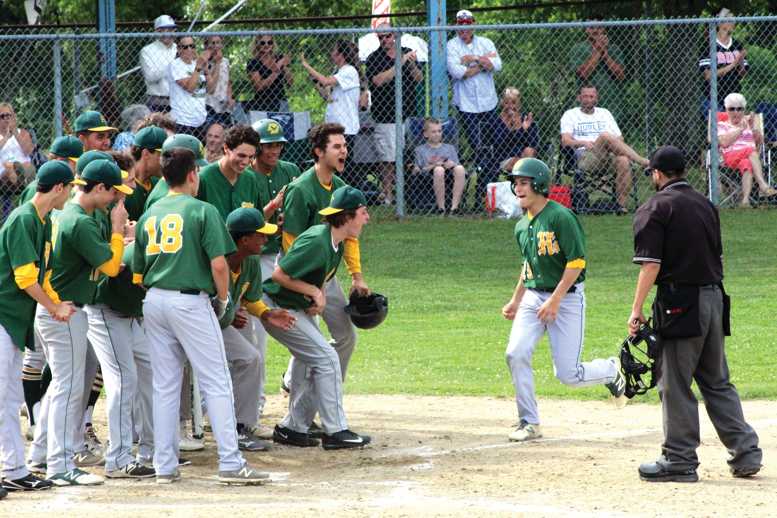 Josh Stravato is greeted by teammates at home plate after blasting a three-run home run in the second inning.