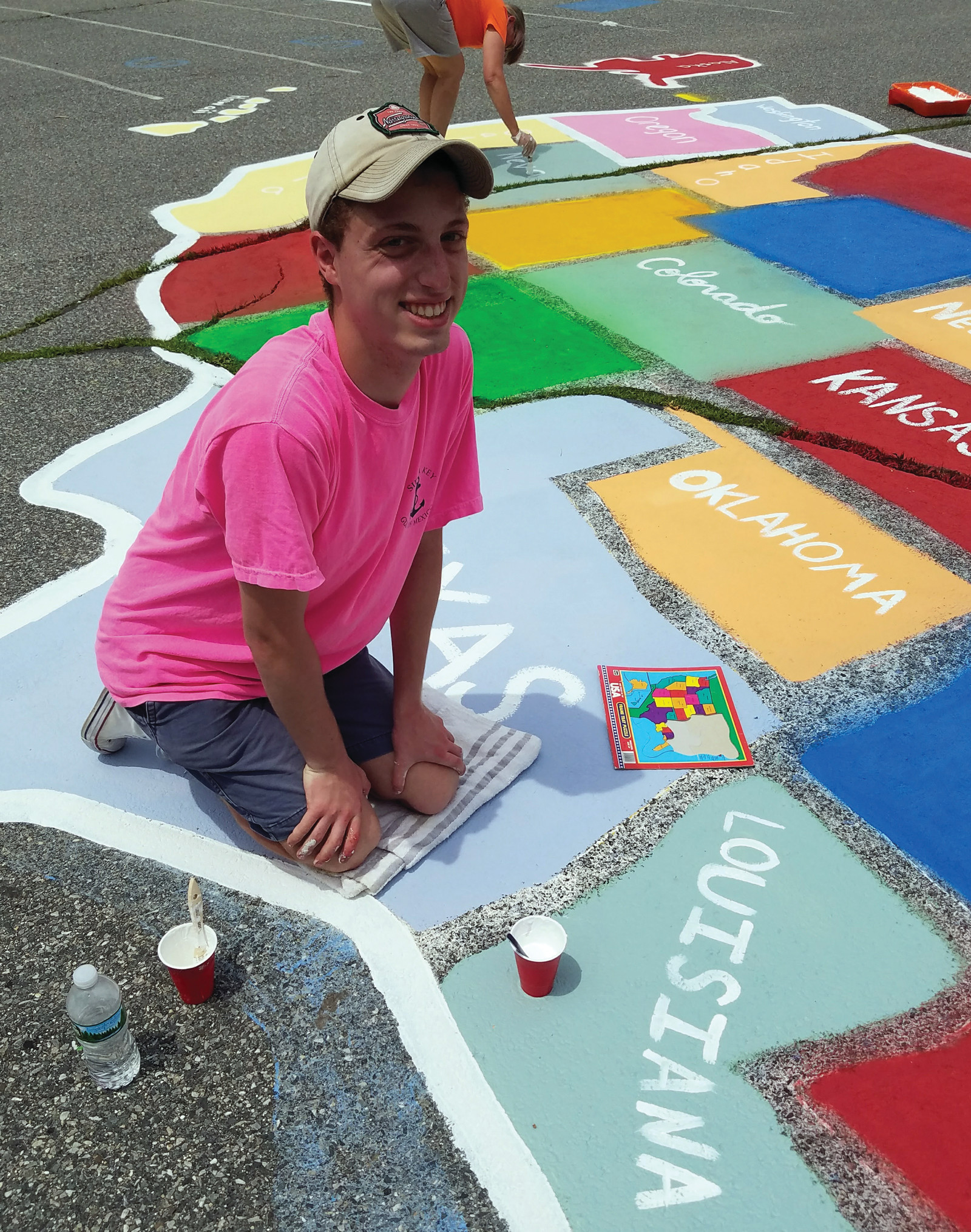 MANY HANDS: Marchetti was able to recruit many of his friends and family to come out on one of the hottest days of the month so far, to paint the blacktop with bright colors and designs for the students at Woodridge School.