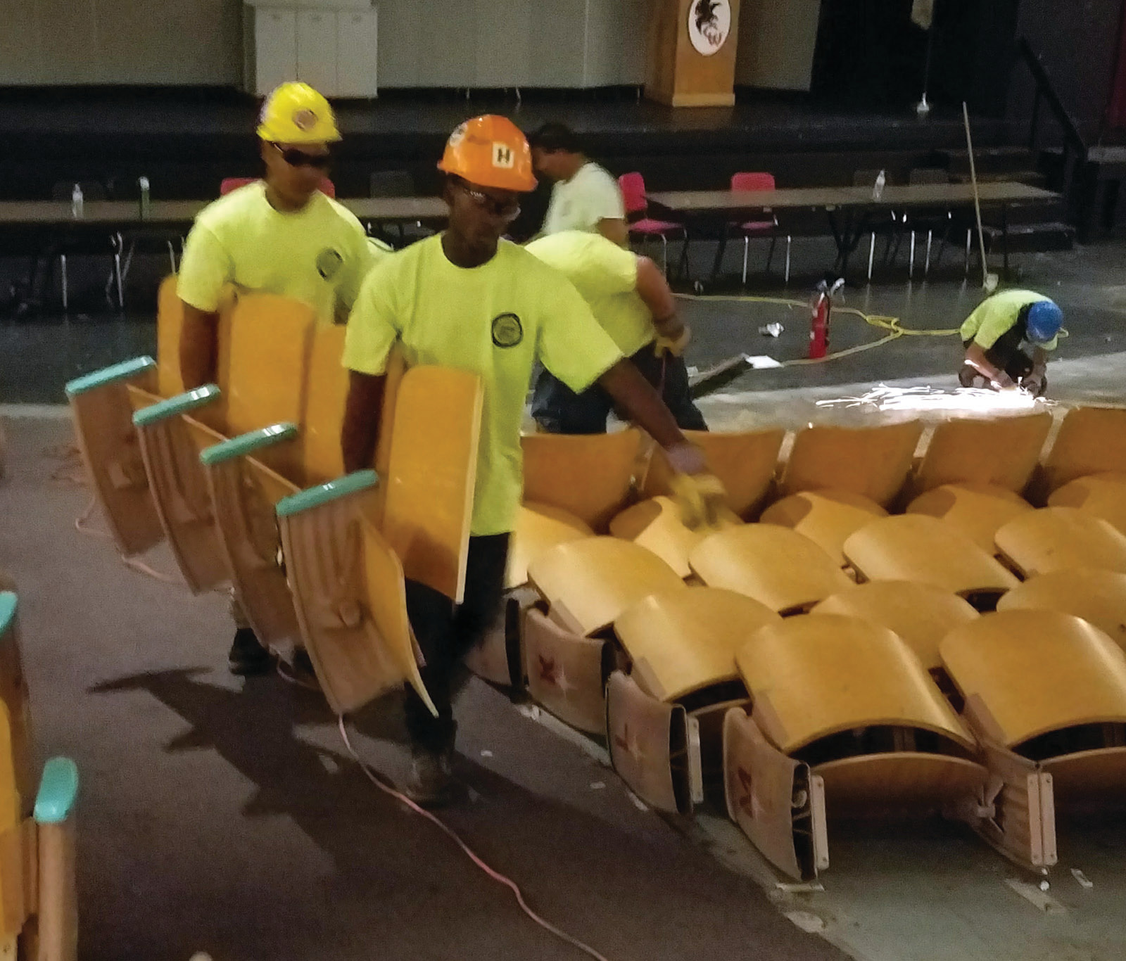 MANY HANDS MAKE LIGHT WORK: The newly minted grads work together to remove approximately 700 seats from the Cranston West auditorium as it undergoes its first renovation in 54 years.