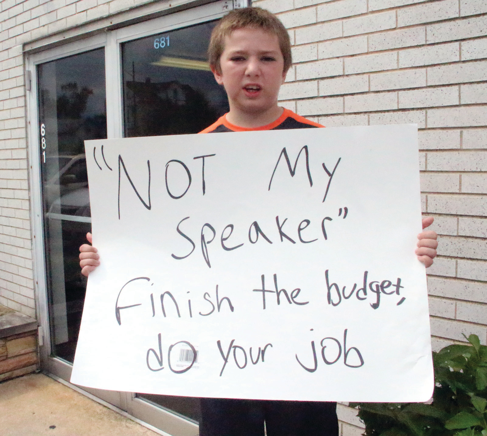 "John Hanley, 10, remained outside the law office of House Speaker Nicholas Mattiello as his father George and others protesting the lack of a state budget went inside to see Mattiello. ""I want him to get back to his job [at the State House],"" John said of Mattiello."