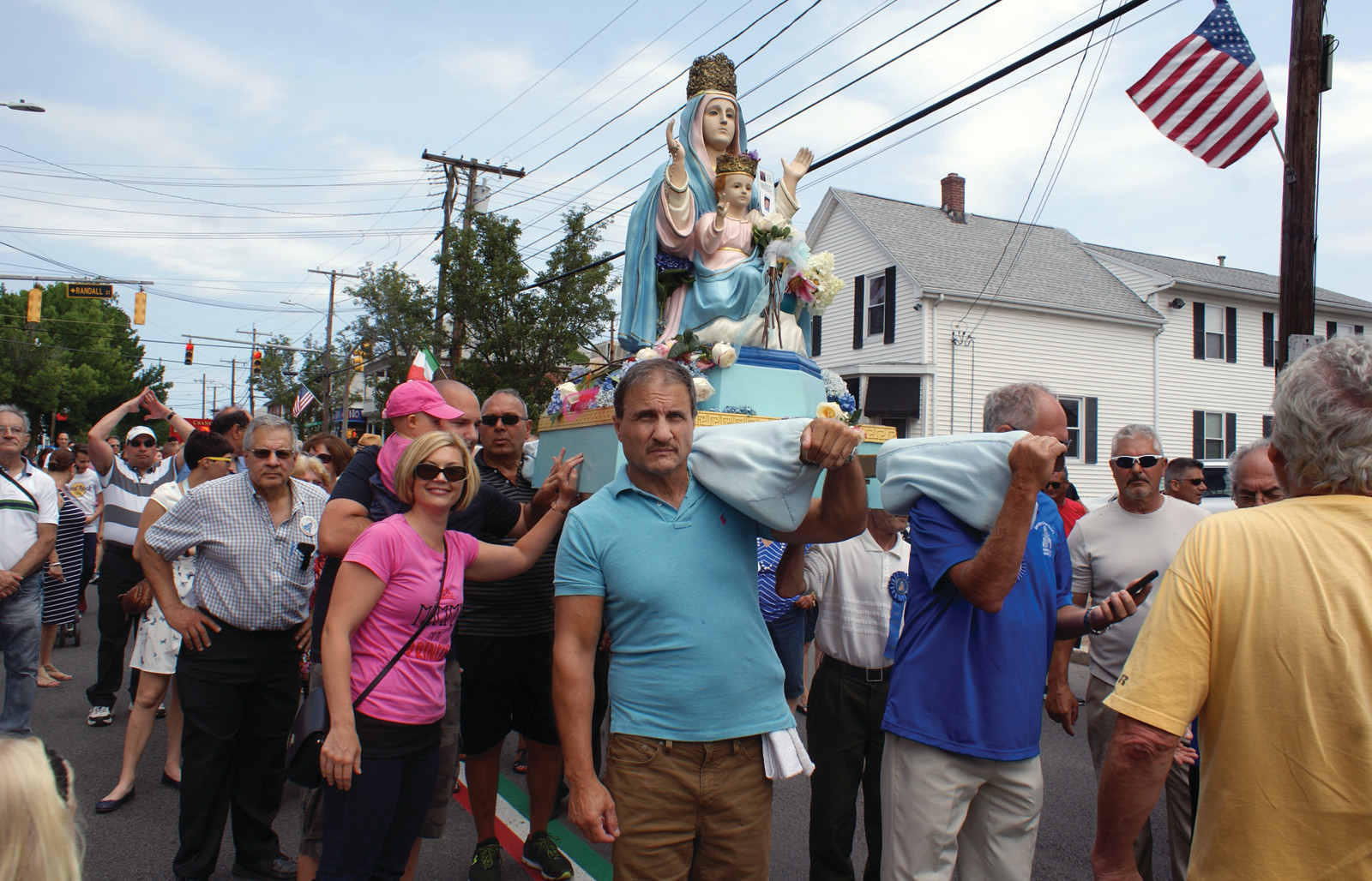 FIRST TIME FOR EVERYTHING: On the left, 1-year-old Sienna Troia leans in with dad David to touch the statue of the Madonna at the St. Mary's Feast Parade on Sunday. Mom Jessica joined them, as it was Sienna's first-ever St. Mary's Feast.