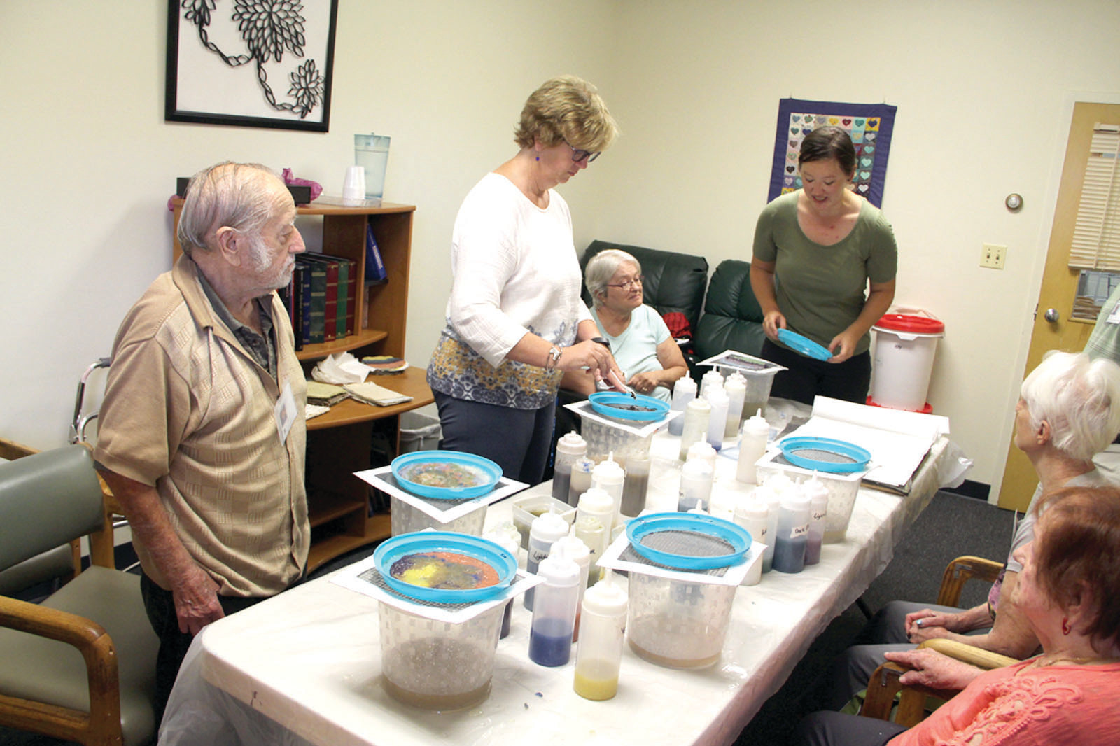 ALL TOGETHER NOW: Residents of the Cornerstone Adult Day Center pose with their handmade paper creations.