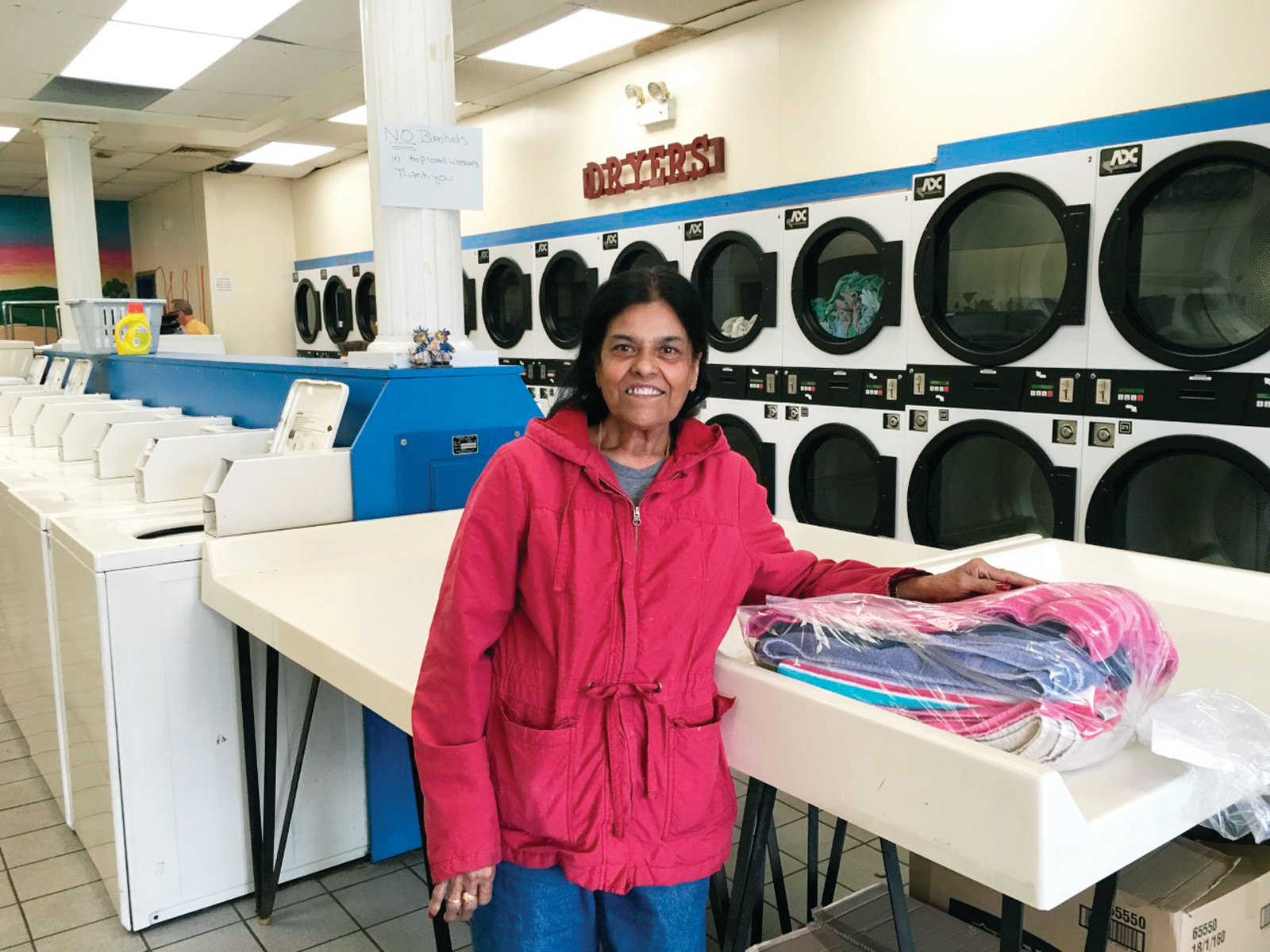 Kaushal Jain is a familiar face at the family-owned business that she and her husband have operated for over twenty-six years ~ here, she is ready to fold a load of clothes, straight from one of the laundromat's modern dryers.