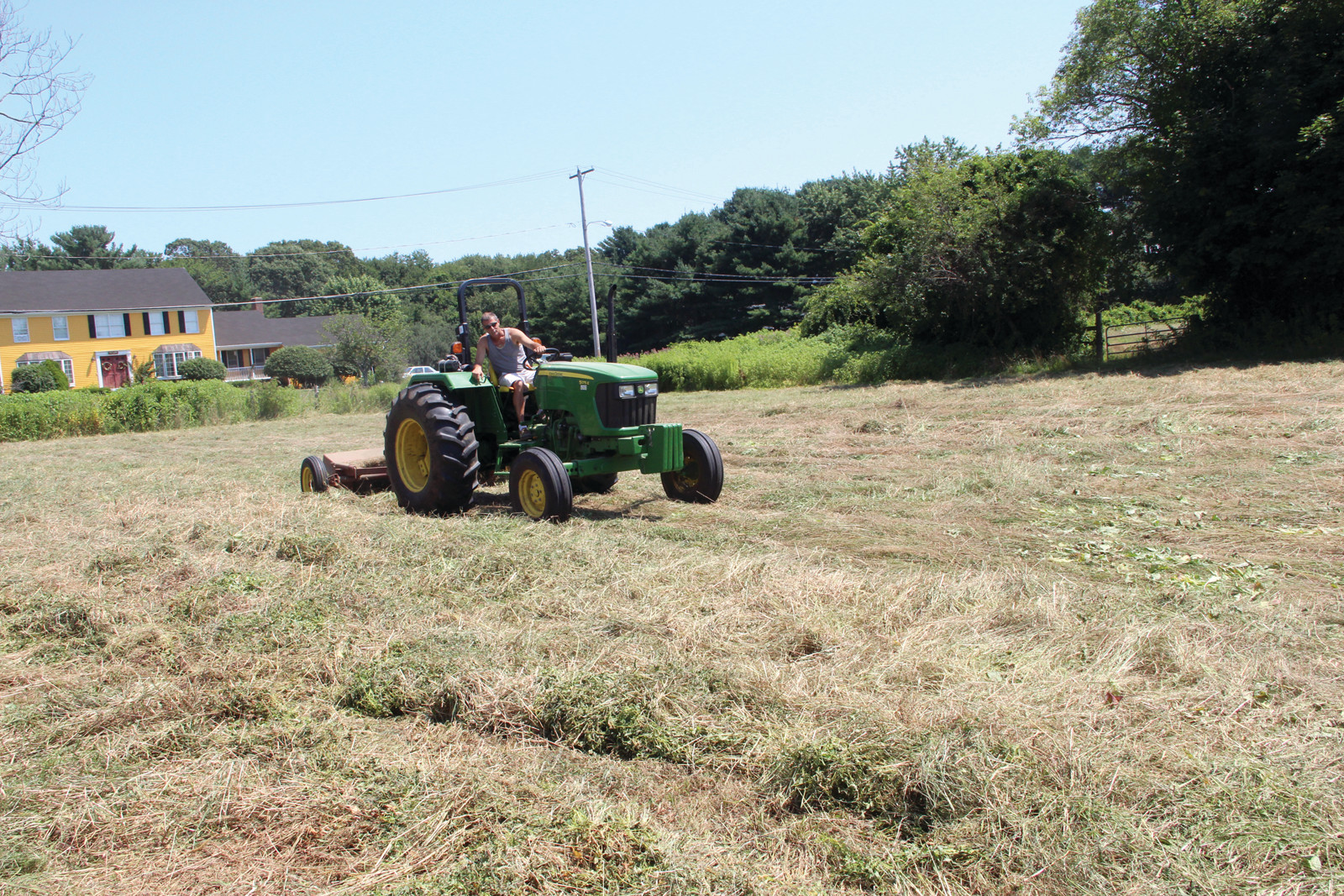 Paul Sullivan crimps hay at Morris Farm in Warwick. Normally, hay production is finished by the last week of June. An extra-rainy spring pushed back that schedule.