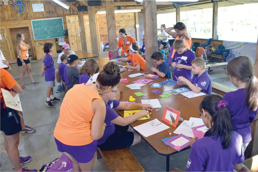 GATHERING AROUND: The Purple Group got creative with arts and crafts in their cabin at camp.