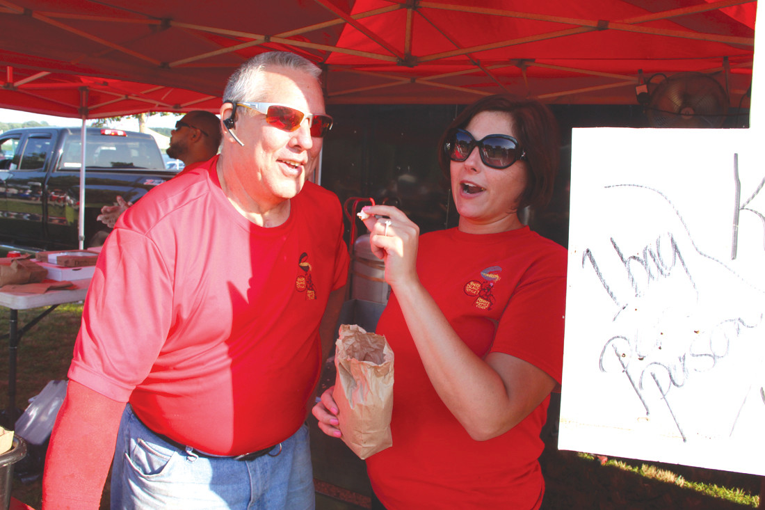 THEY WERE POPPING: Free bags of Poppy's Gourmet Kettle Corn were a hit at National Night Out. Here, Steve Gilman, owner, gets a sample from his daughter Emily Hermann.