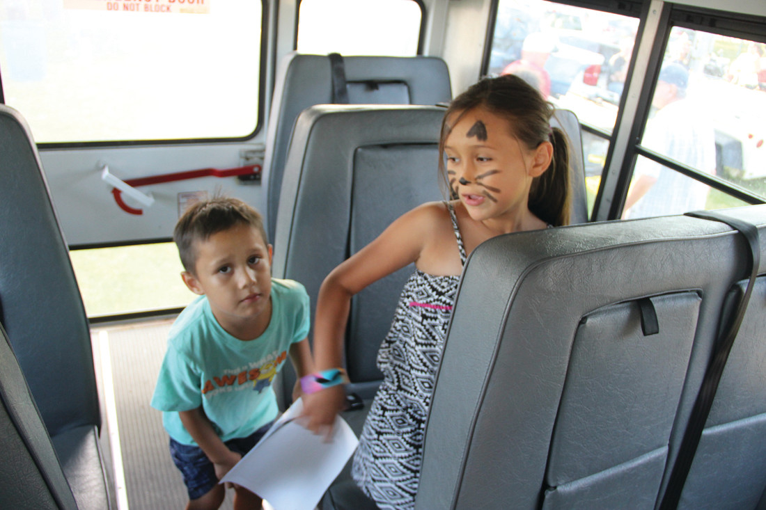 THEY LOVE THE BUS: Jayden and his sister Kayle Perez Borders were thrilled to find a First Student school bus at National Night Out.