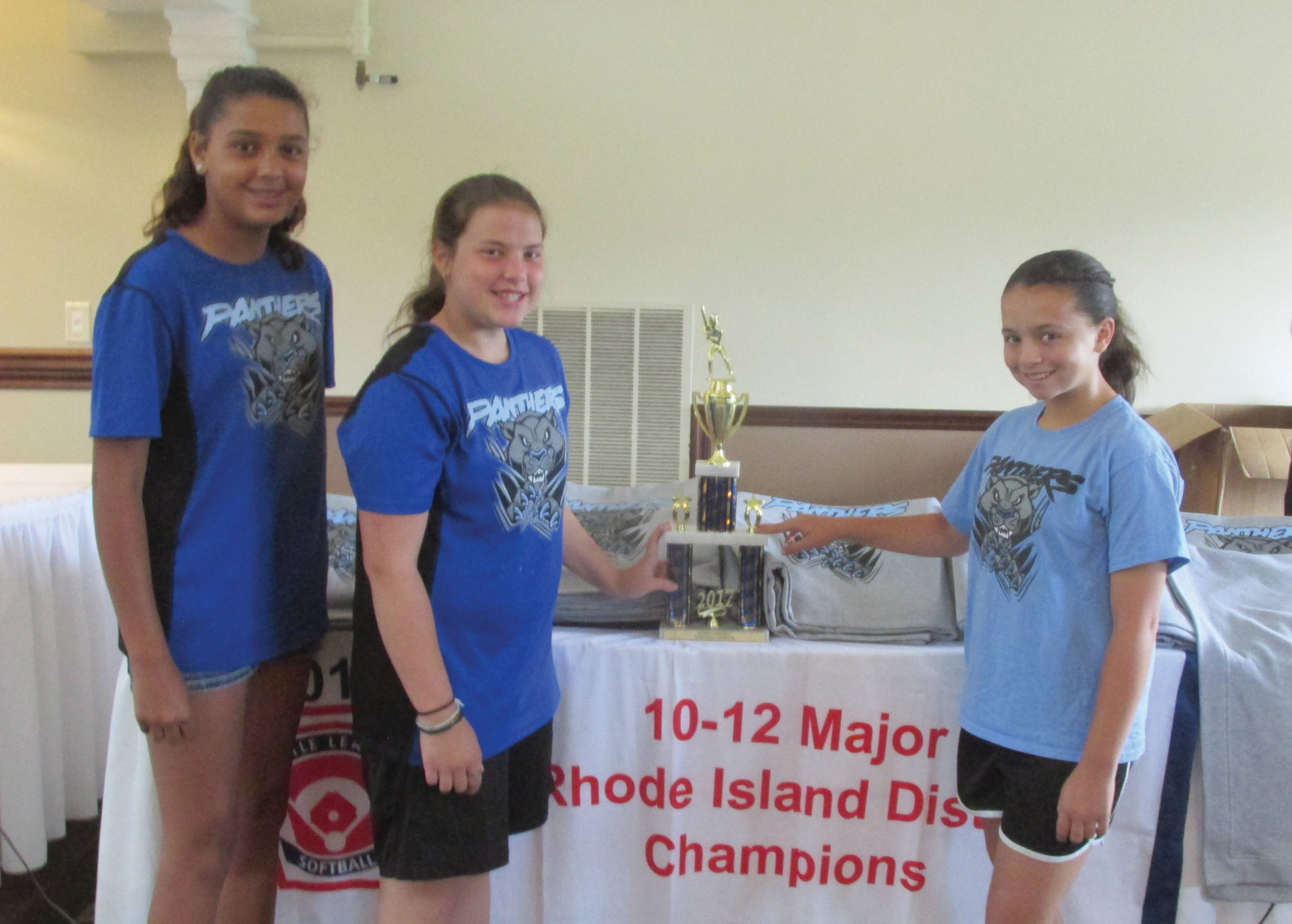 TALENTED TRIO: These three girls - Alyssa Andrade, Gianna Robinson and Hannah Calabro - are standing in front of the R.I. Little League District 4 Championship trophy that was on display Saturday at Cranston Country Club.