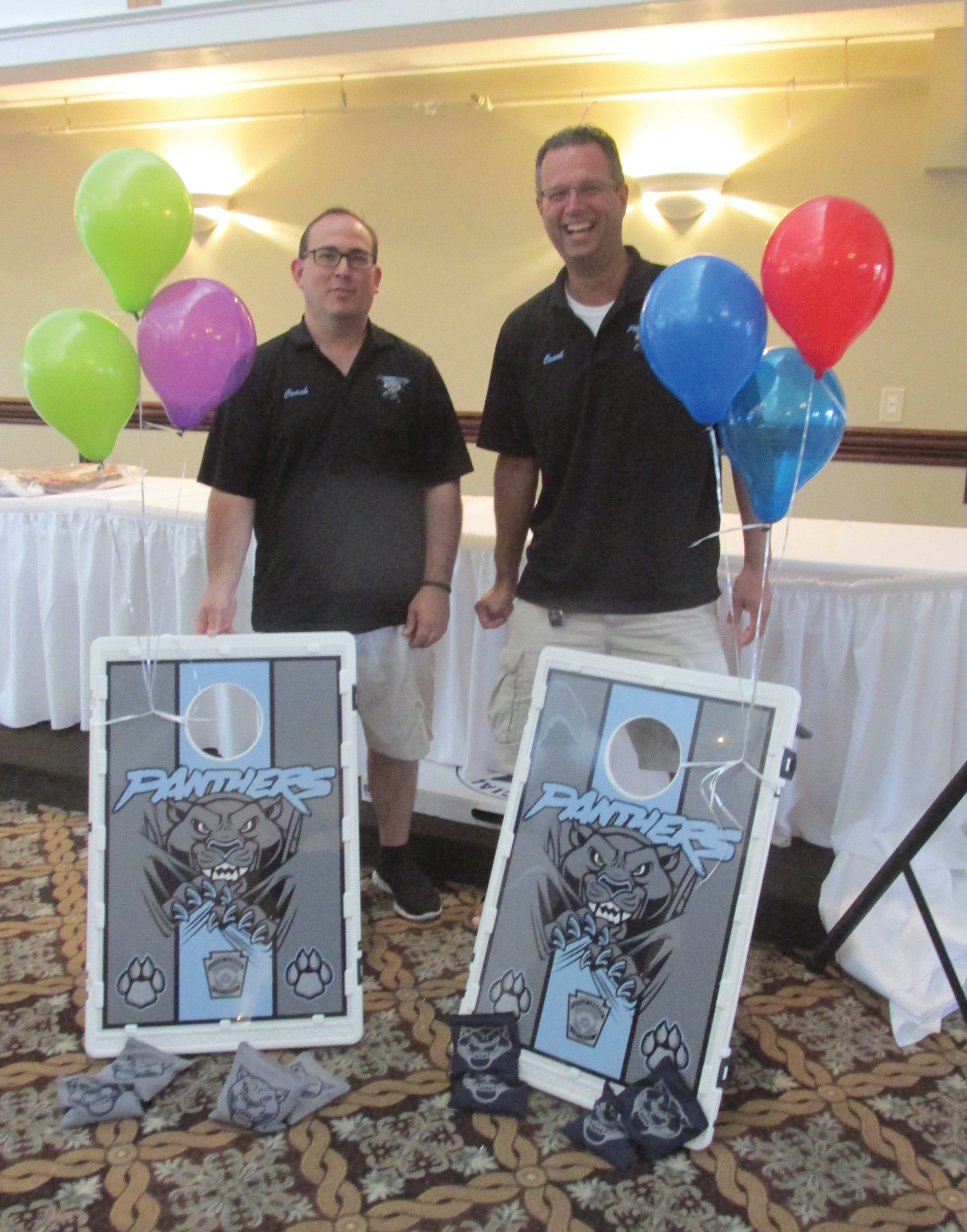 COACHES CORNER: Johnston Girls Softball League coaches Derek Carrier and Mike Alvin enjoy a lighter moment while holding the highly-popular cornhole boards that were won by the Pilkington family during Saturday's banquet.