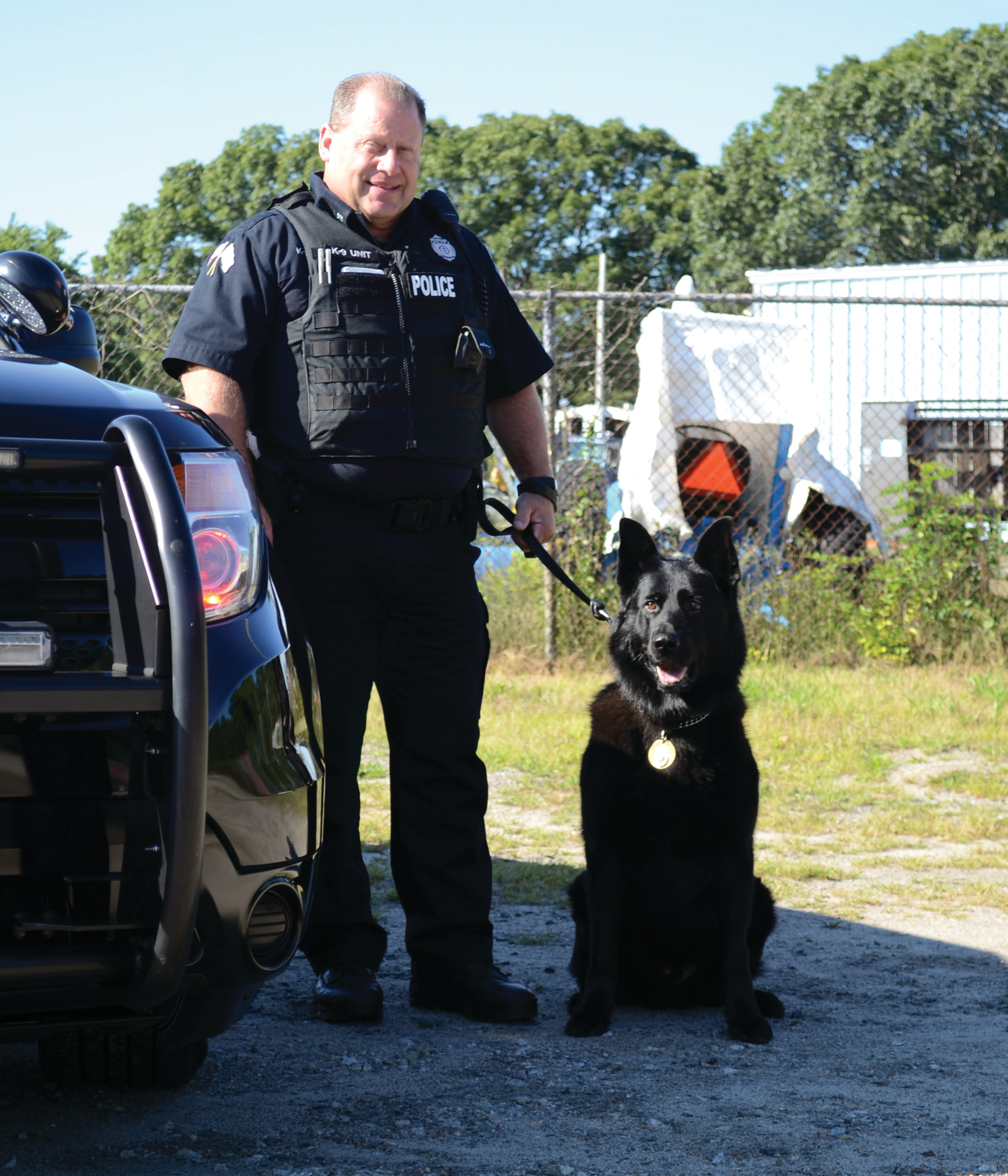 FOXTROT: K-9 officer Fox, an all-black German Shepherd, standing with his human partner, Officer Paul Wells.