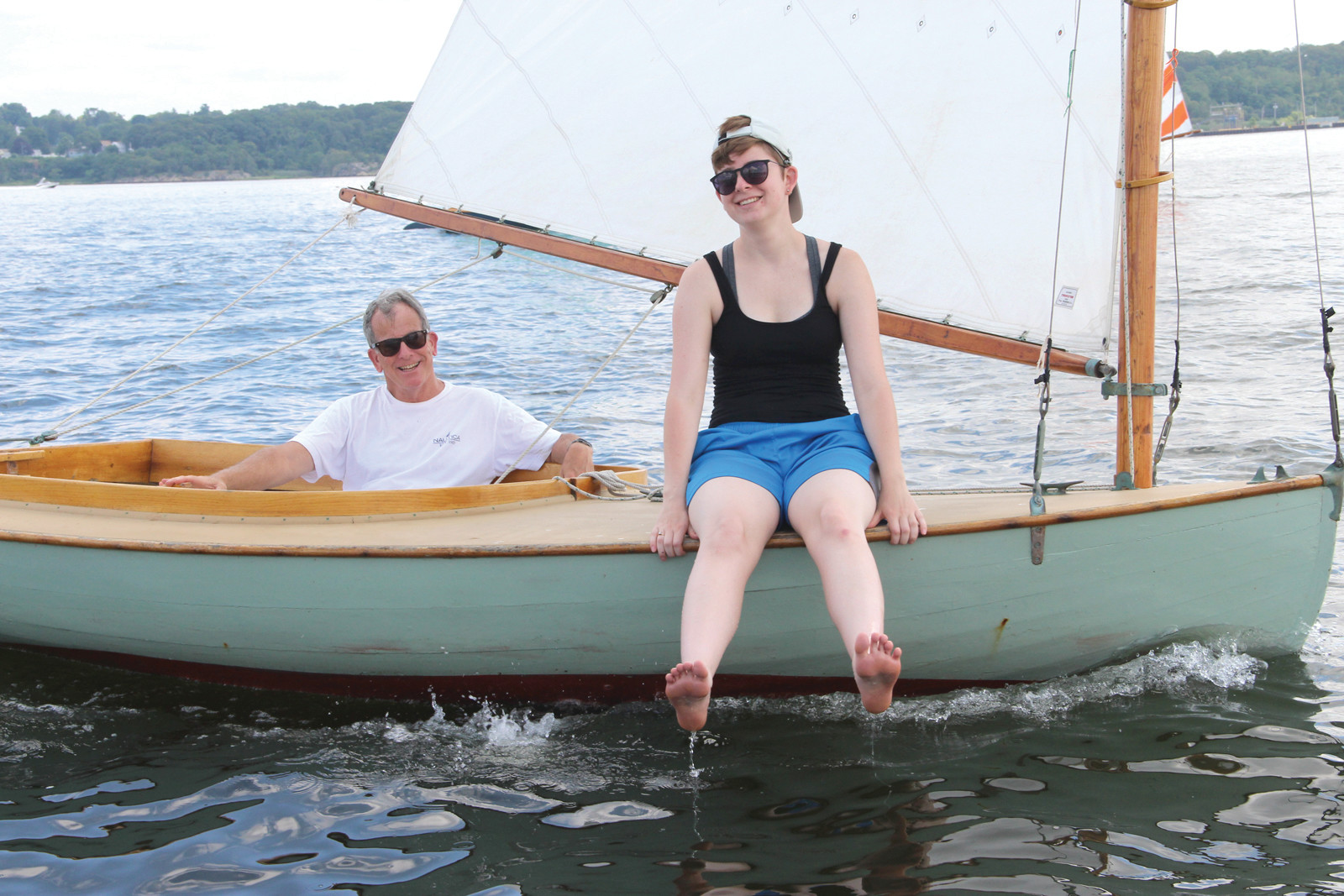 KEEPING COOL: Hope Lanphear, who was the skipper of Nuisance, cools her feet as her father Jeffery Lanphear takes the tiller prior to the start of a race.