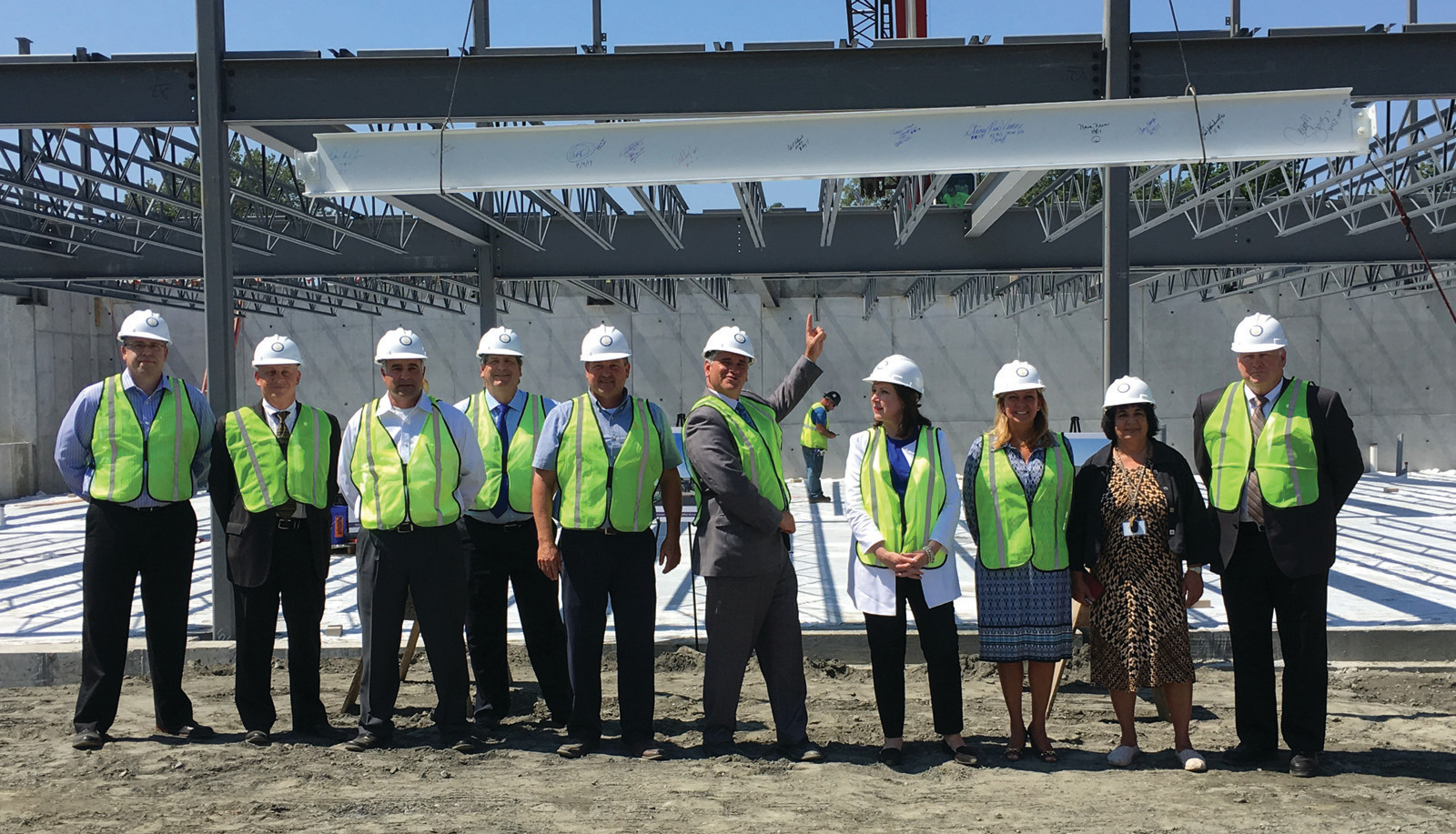 PROUD OF THEIR WORK: Attorney General Peter Kilmartin points up at the steel beam that he and his employees signed at the new Customer Service Center's topping off ceremony last Wednesday.