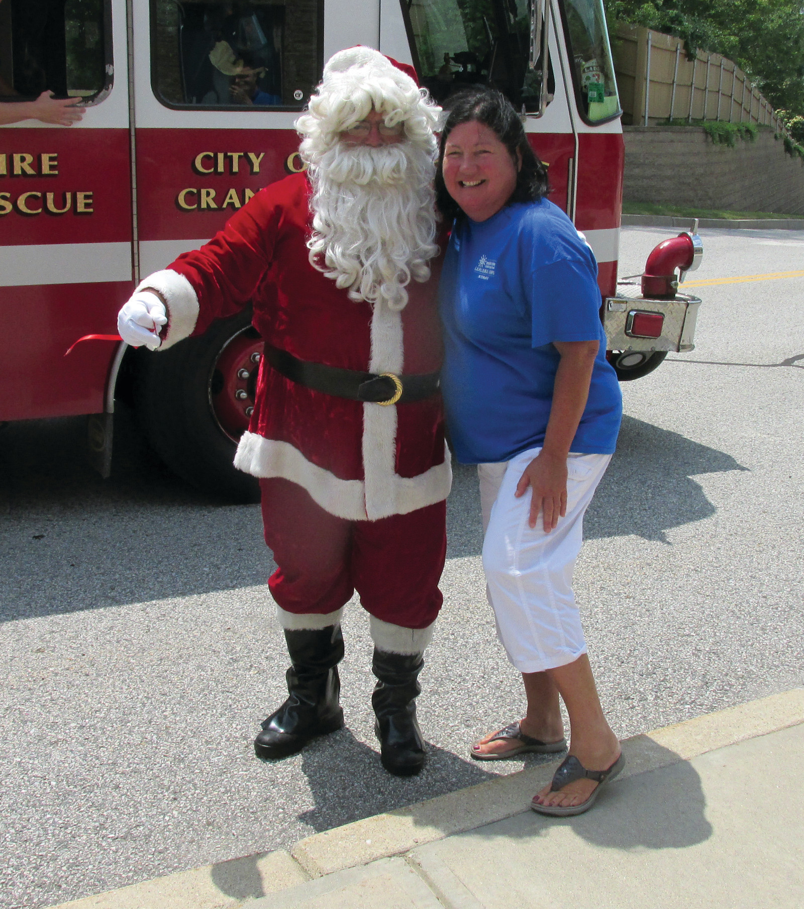 GRAND GREETING: Immaculate Conception teacher Carol McPhillips enjoys a rare moment in the middle of the summer, as she greets Santa Claus himself during the Summer Explore program's Christmas in July in Cranston.