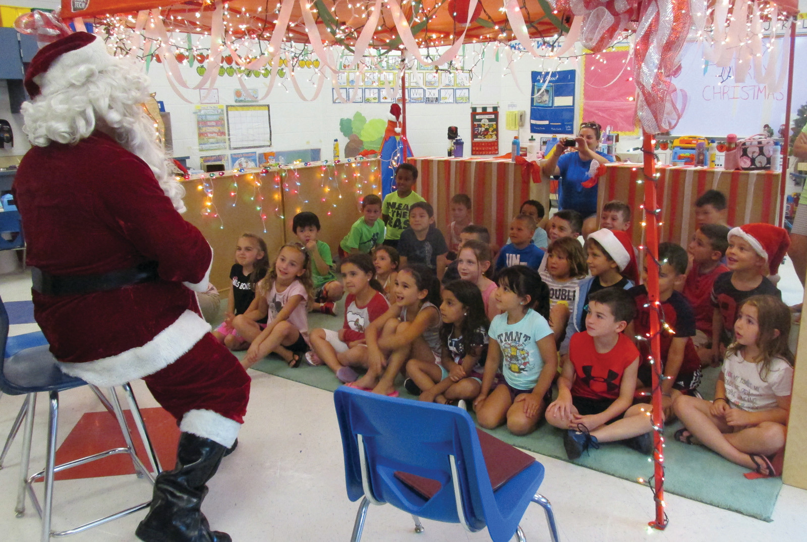 SPECIAL REQUESTS: Santa Claus sits on a chair and fields a variety of special requests from children who attended the unique Summer Explore program.