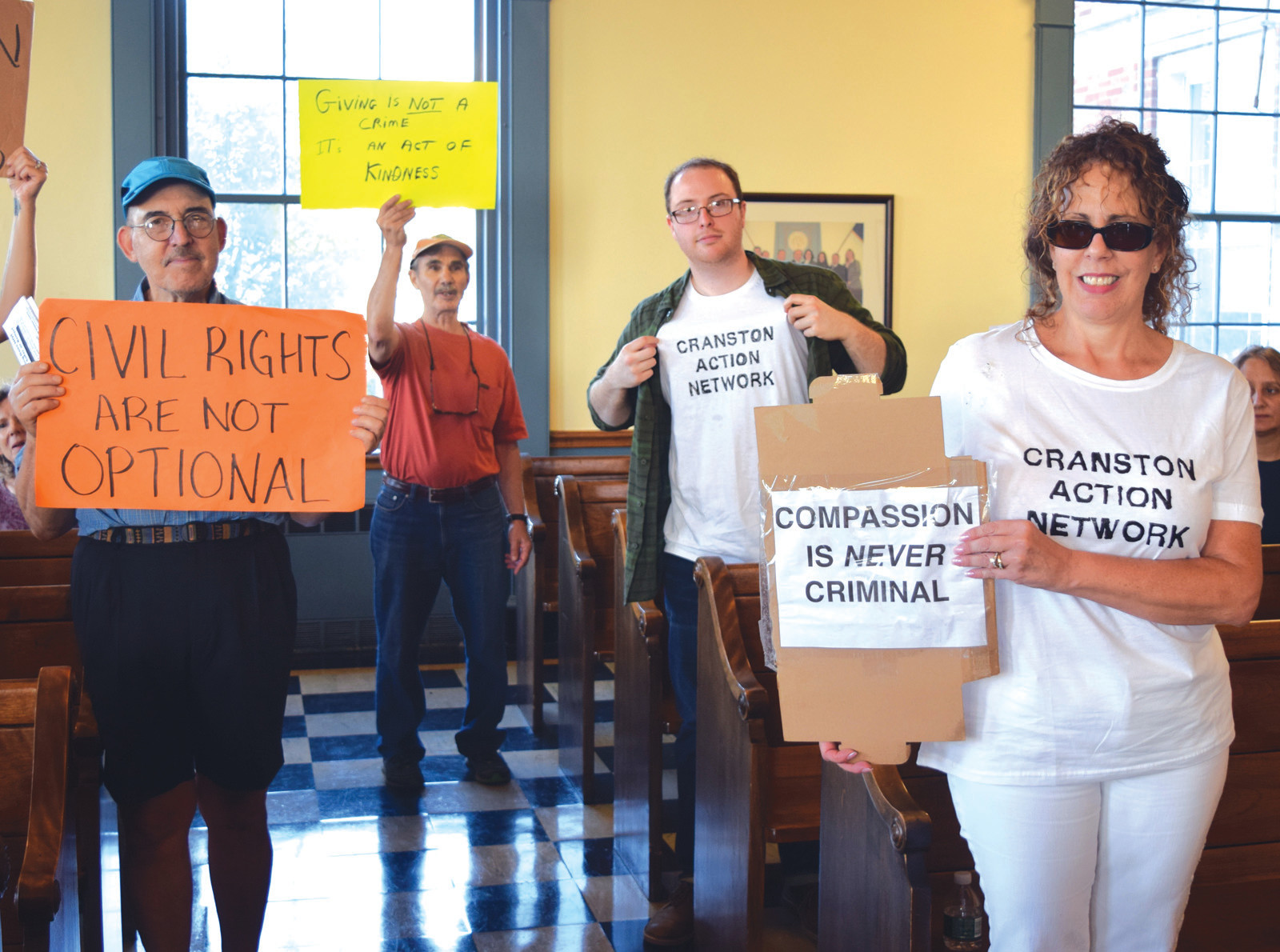 TAKING ACTION: John Donegan, in the middle holding up his shirt, and members of the Cranston Action Network took over the chambers on Thursday as the City Council went into executive session.