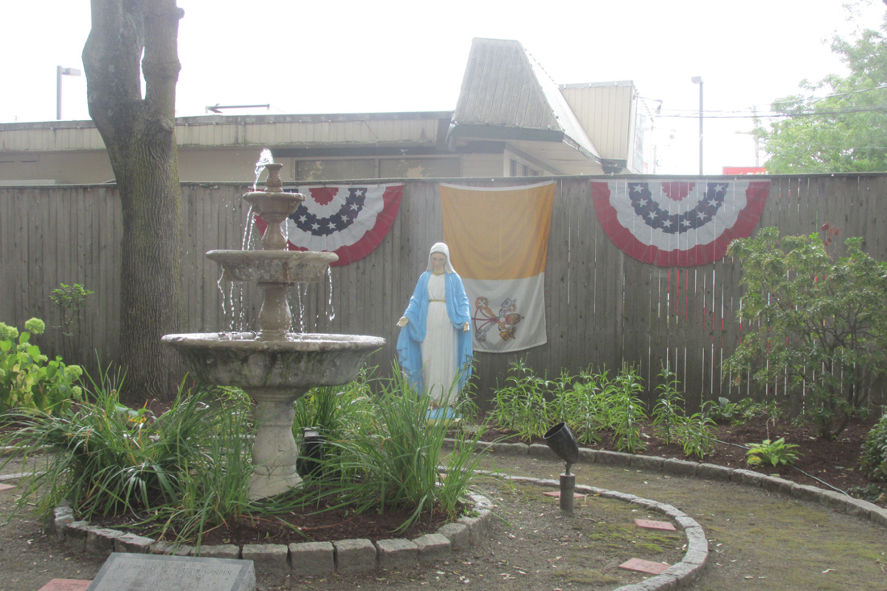 SPECIAL SIGNS: The St. Francis Garden located next to Saint Rocco Church is adorned with American and Italian flags and bunting.