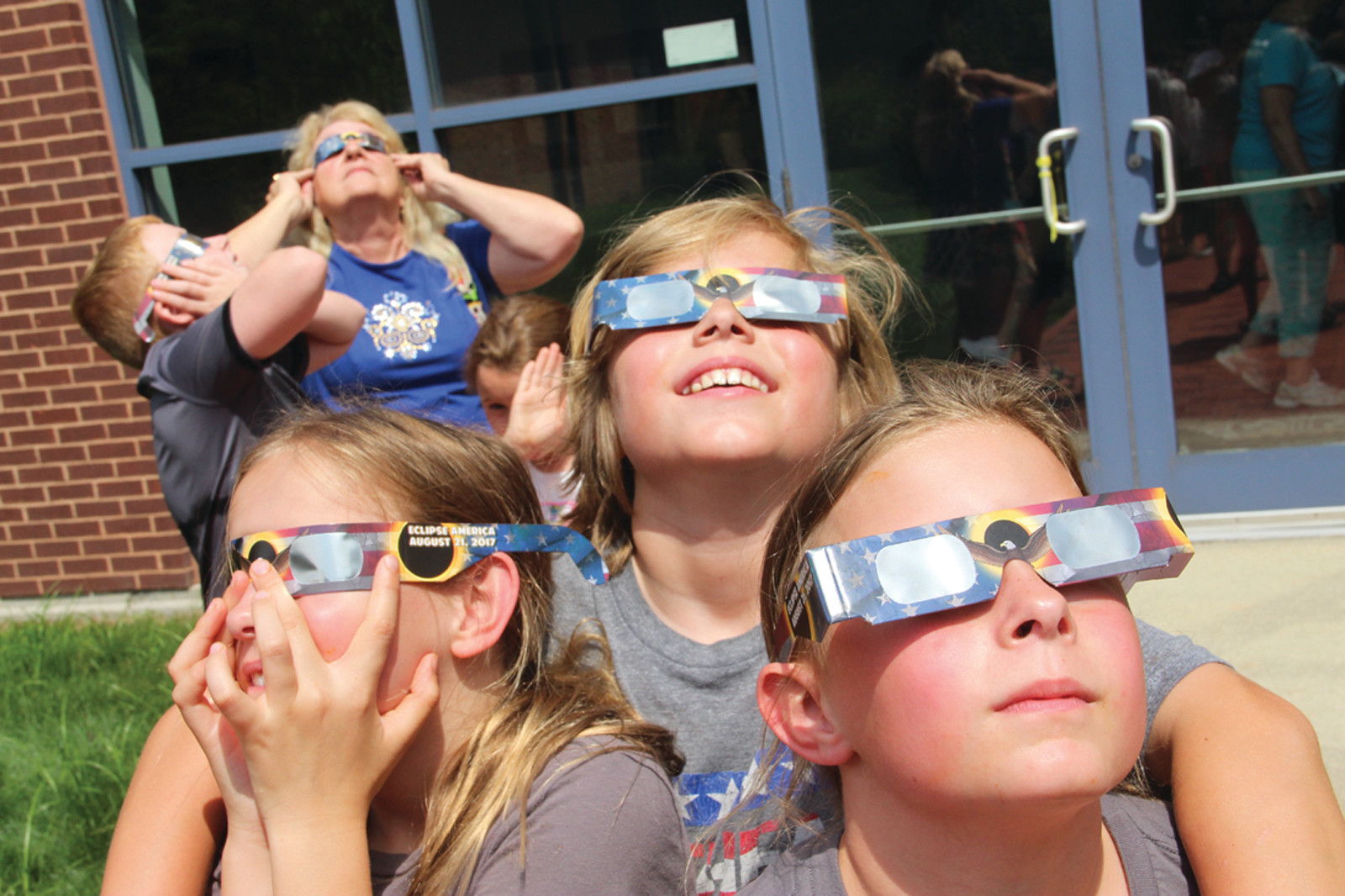 A LITTLE SUN MEANS TRIPLE THE FUN: Triplets Reilly, Zachary and Chloe Darrow look at the eclipse through their special glasses. Below, the sun as it appeared at the height of the eclipse in Rhode Island.