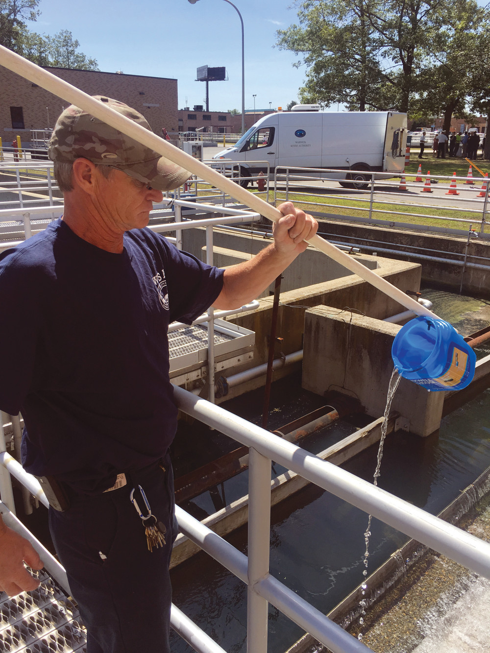 NO MORE WASTE: Gwin Cox, lead operator at the facility for the Warwick Sewer Authority, pours water from a testing bucket during the last step of the wastewater treatment process. The water here is ready to be released back into the Pawtuxet River.